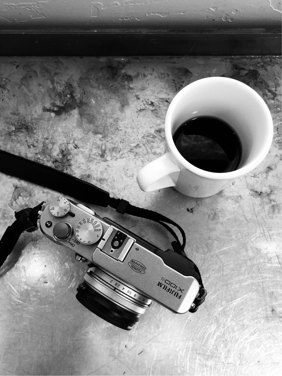 Black and white photo of a coffee cup and small camera.