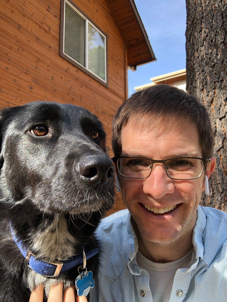 Selfie of the dog and me. She has black fur and a long snout and I have glasses, brown hair, and AirPods in.