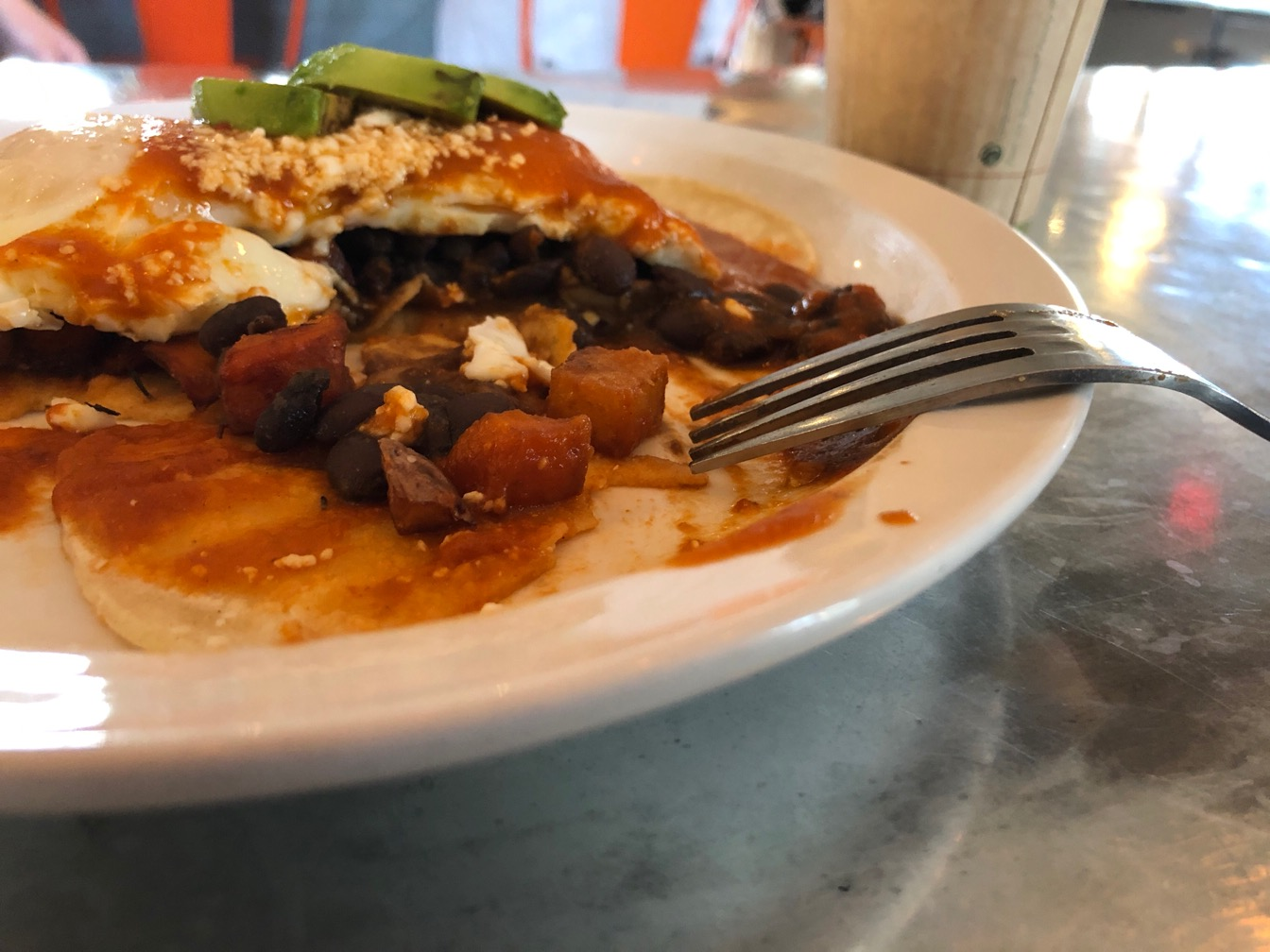 Half eaten plate of huevos rancheros with a cup of coffee.