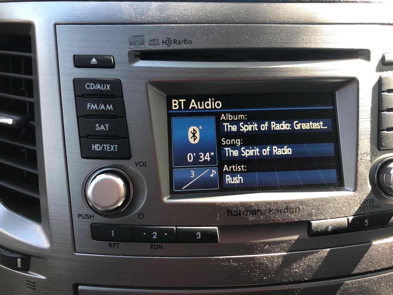 Photo of car stereo display; The Spirit of Radio by Rush is playing.