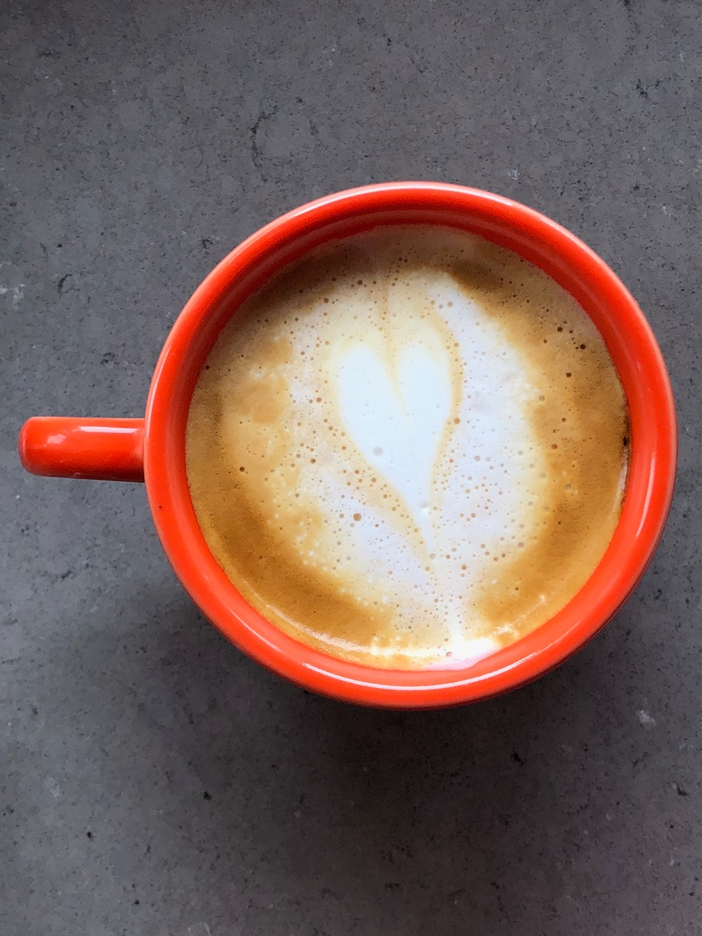 Top down photo of a cappuccino in an orange cup, with a light heart poured in the center.