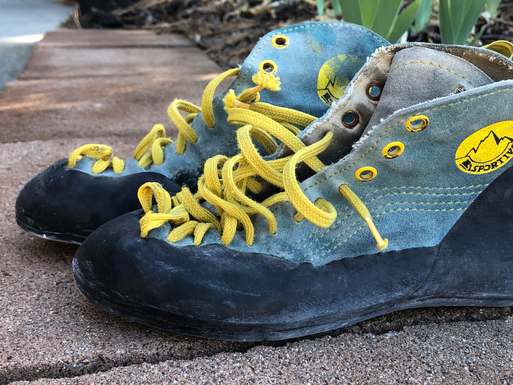 Photo of an old pair of La Sportiva climbing shoes, faded blue with yellow laces.