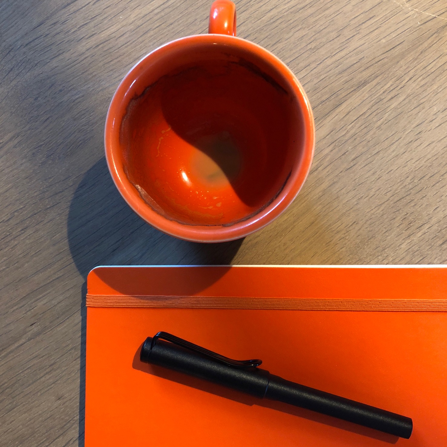 Empty orange coffee cup next to an orange-covered notebook and Lamy pen.