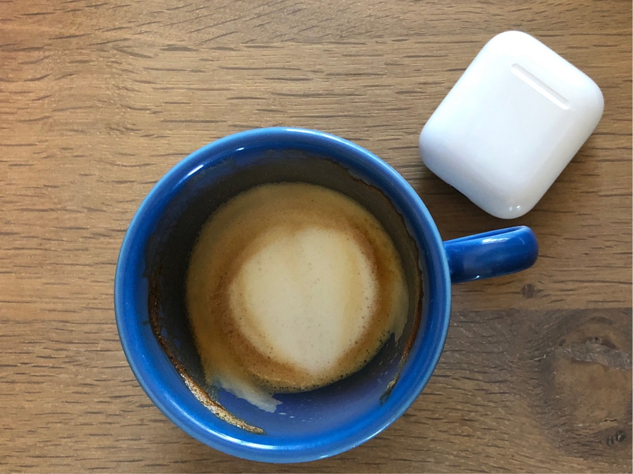 Blue almost empty coffee mug and an AirPods case on a wooden table.