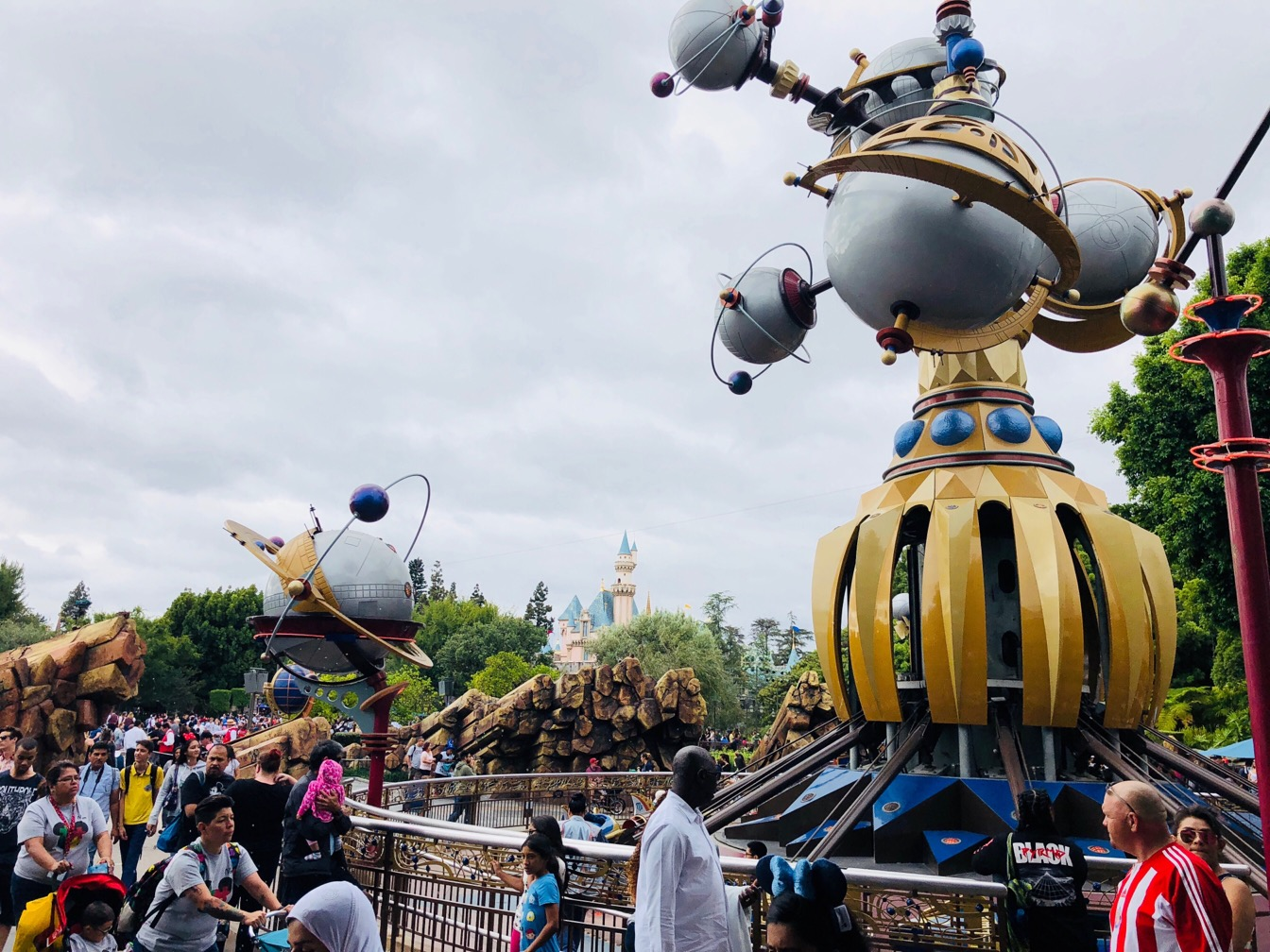 Photo of the Disney castle, taken with space age ride in the foreground.