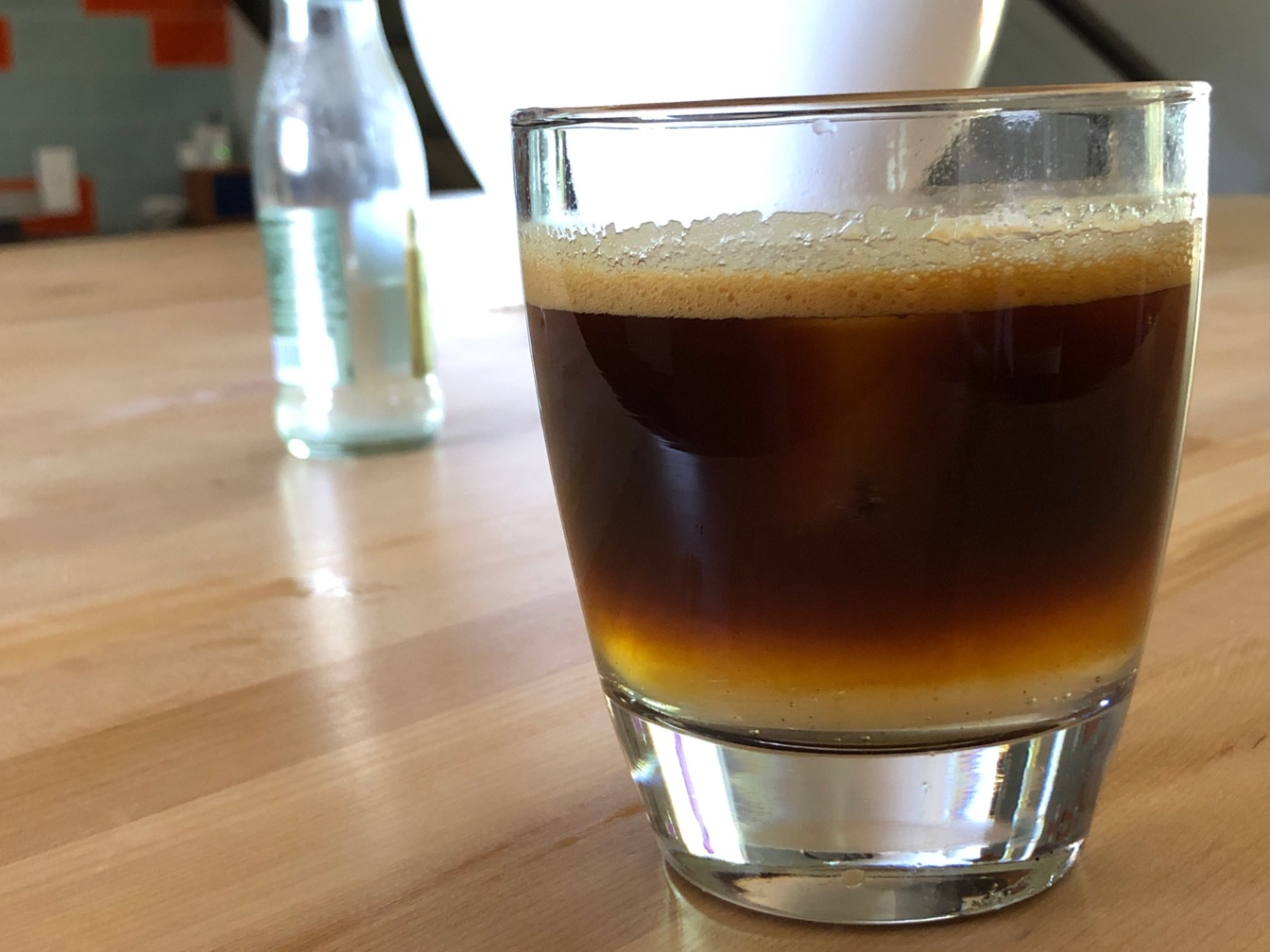 Glass of iced espresso and ginger beer on a wooden xounter