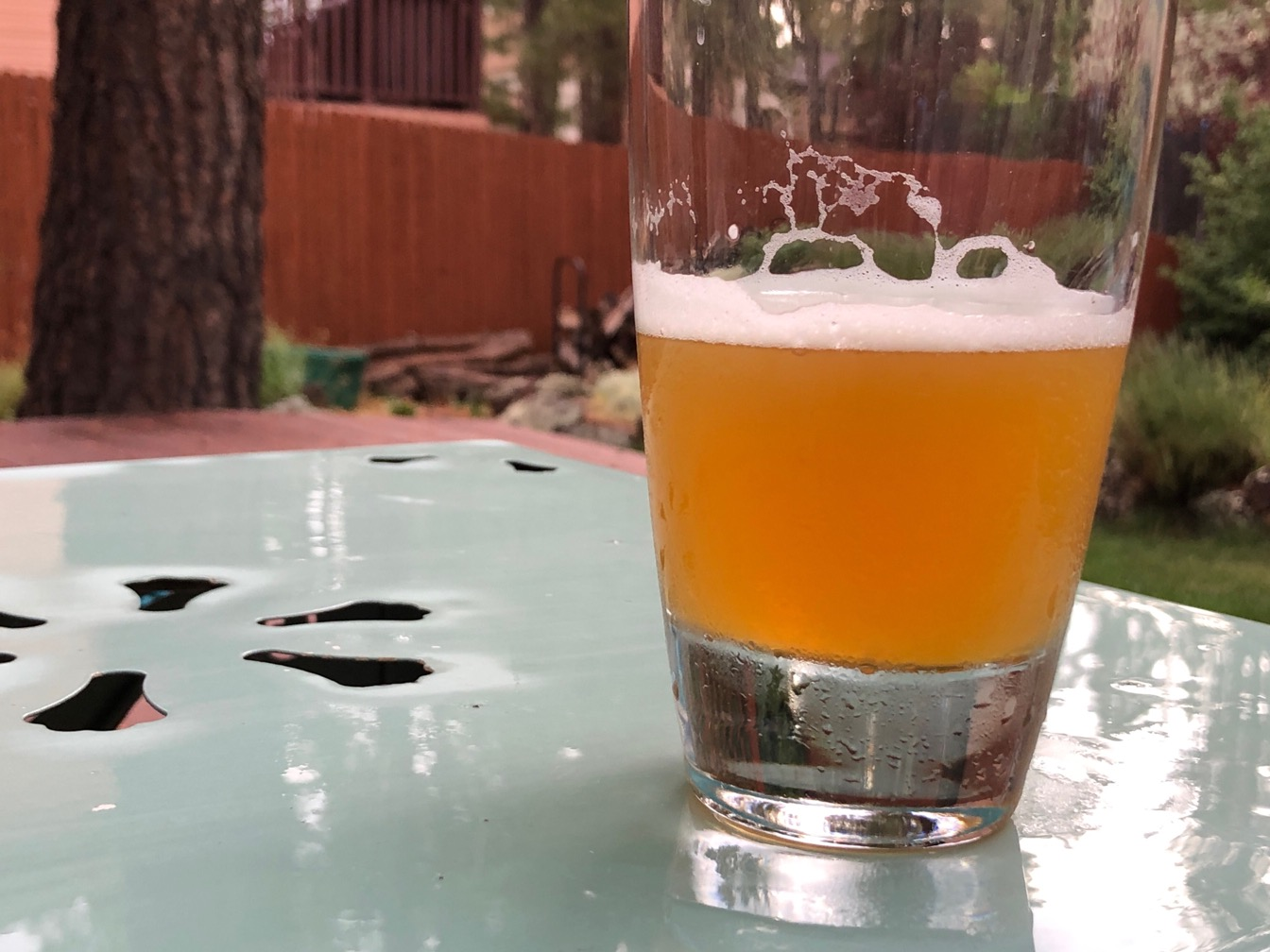 Photo of a glass of beer on a rain-wet table with lawn in the background.
