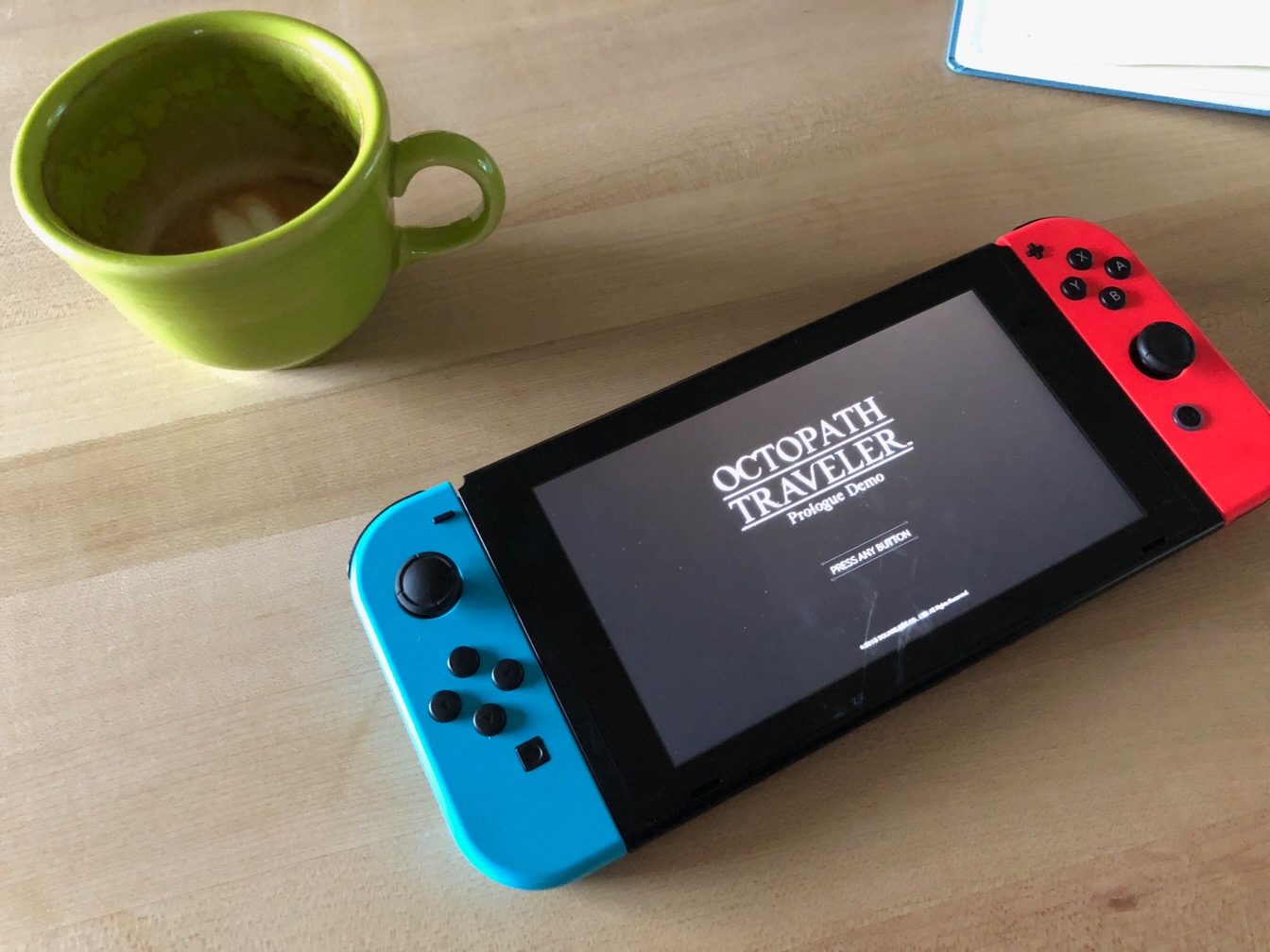 Photo of a mostly empty cappuccino cup and a Nintendo Switch on a wooden counterpoint.