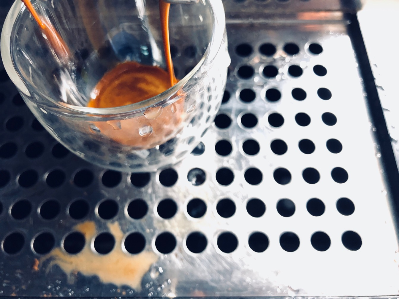 Photo looking down into an espresso cup that has just begun to be filled from a portafilter.