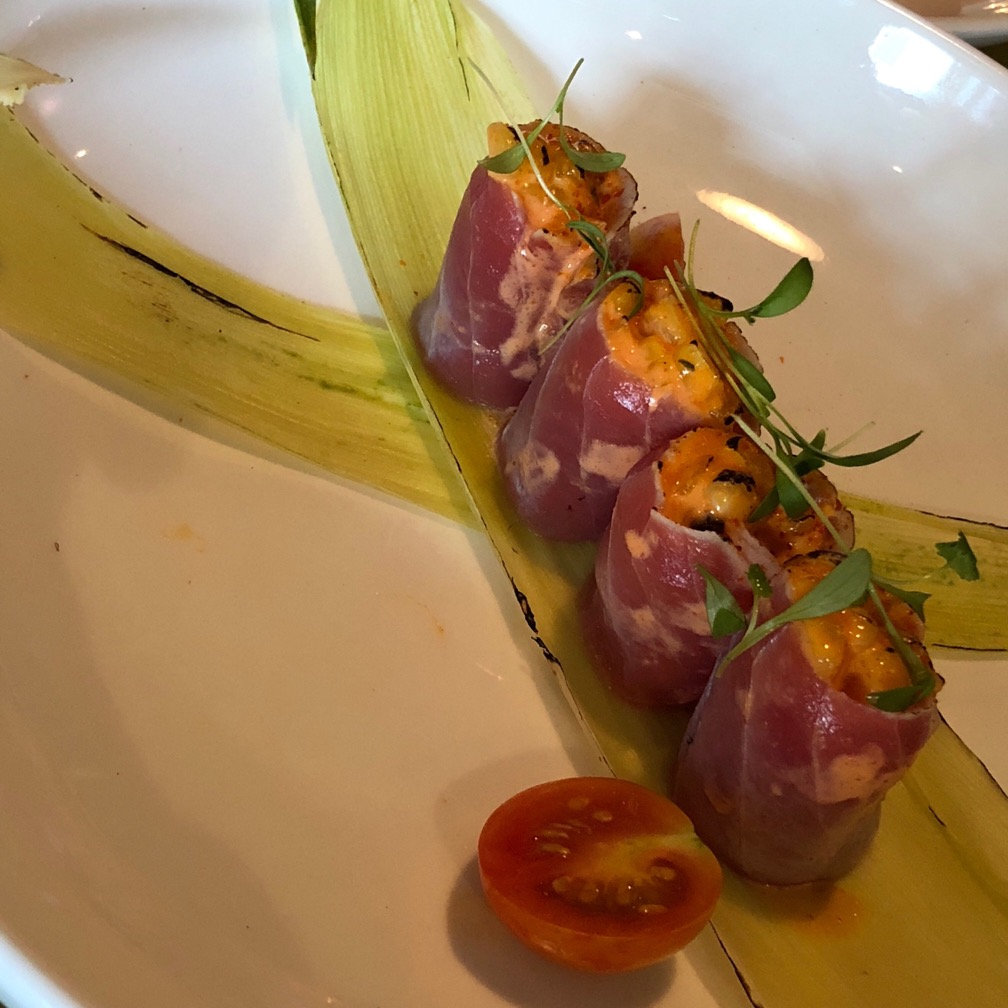 "Photo of four ""tuna corn"" servings laid out on a piece of corn husk: red thin slices of tuna rolled around roasted corn."