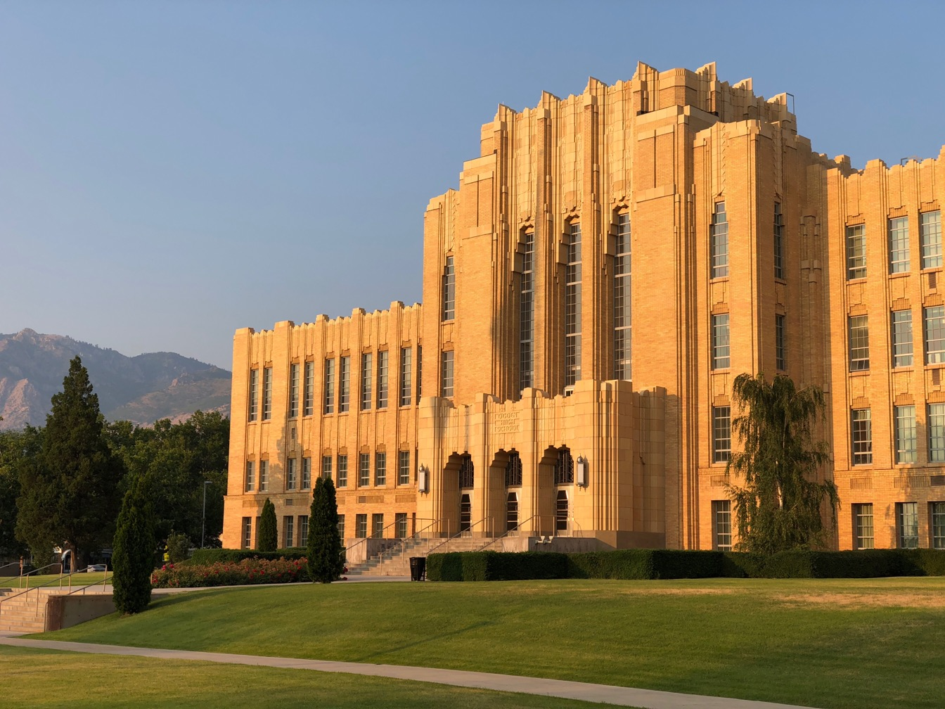 A photo of an art Deco style high school with evening light and mountains behind.