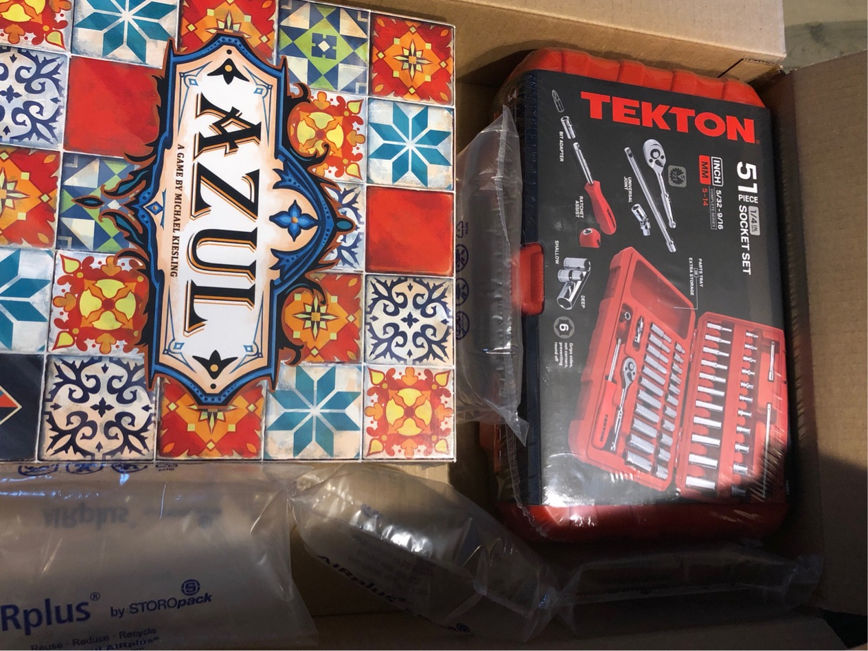 Photo of the board game Azul and a socket wrench set in a shipping box.