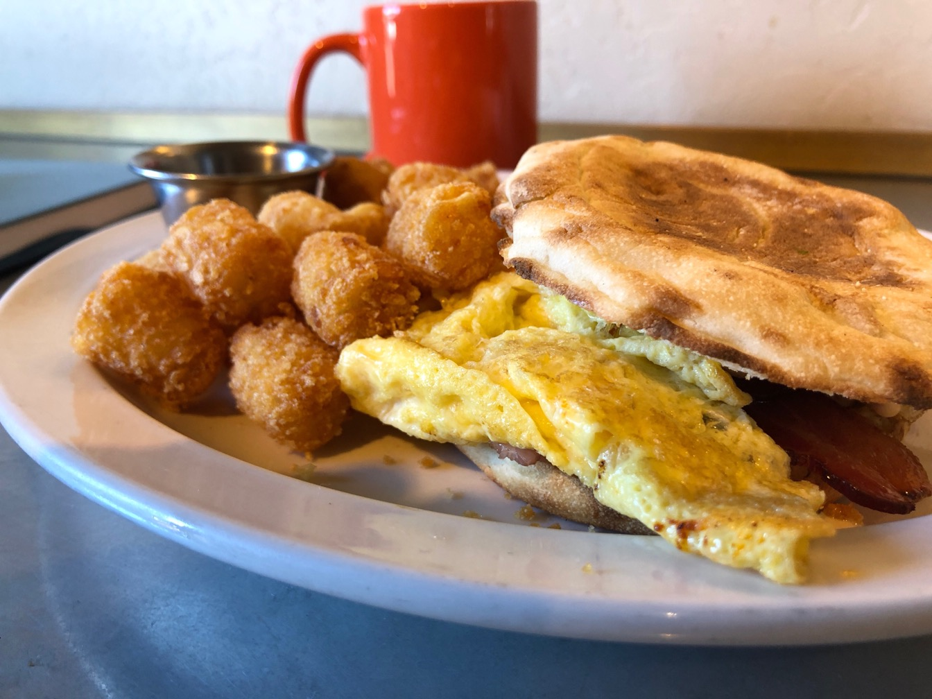 Photo of an English muffin egg sandwich with tater tots and orange coffee cup.
