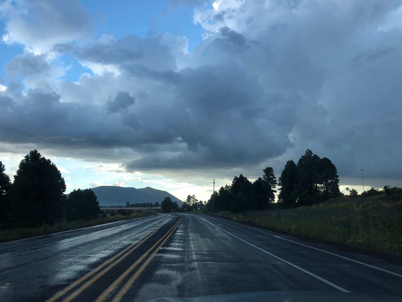 Clouds over mountains and a wet road in morning light.