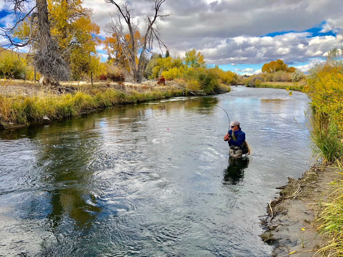 Photo of a man fishing hip deep in a river.