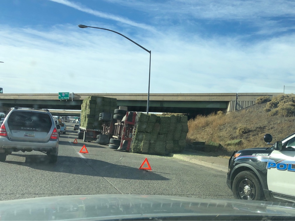 Photo of an overturned trailer full of hay bales.