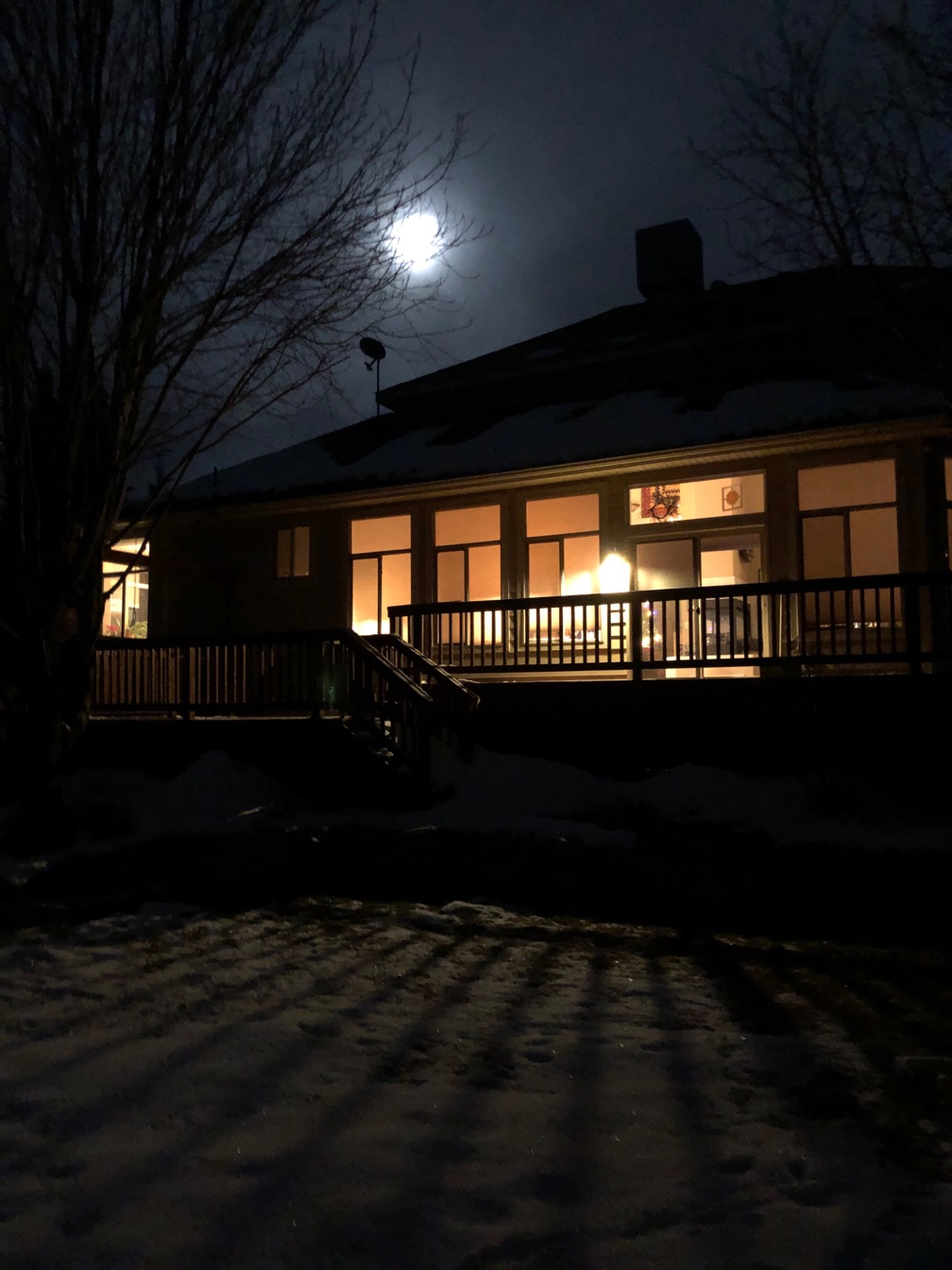 Photo of a house with lights shining through the windows and the moon overhead.