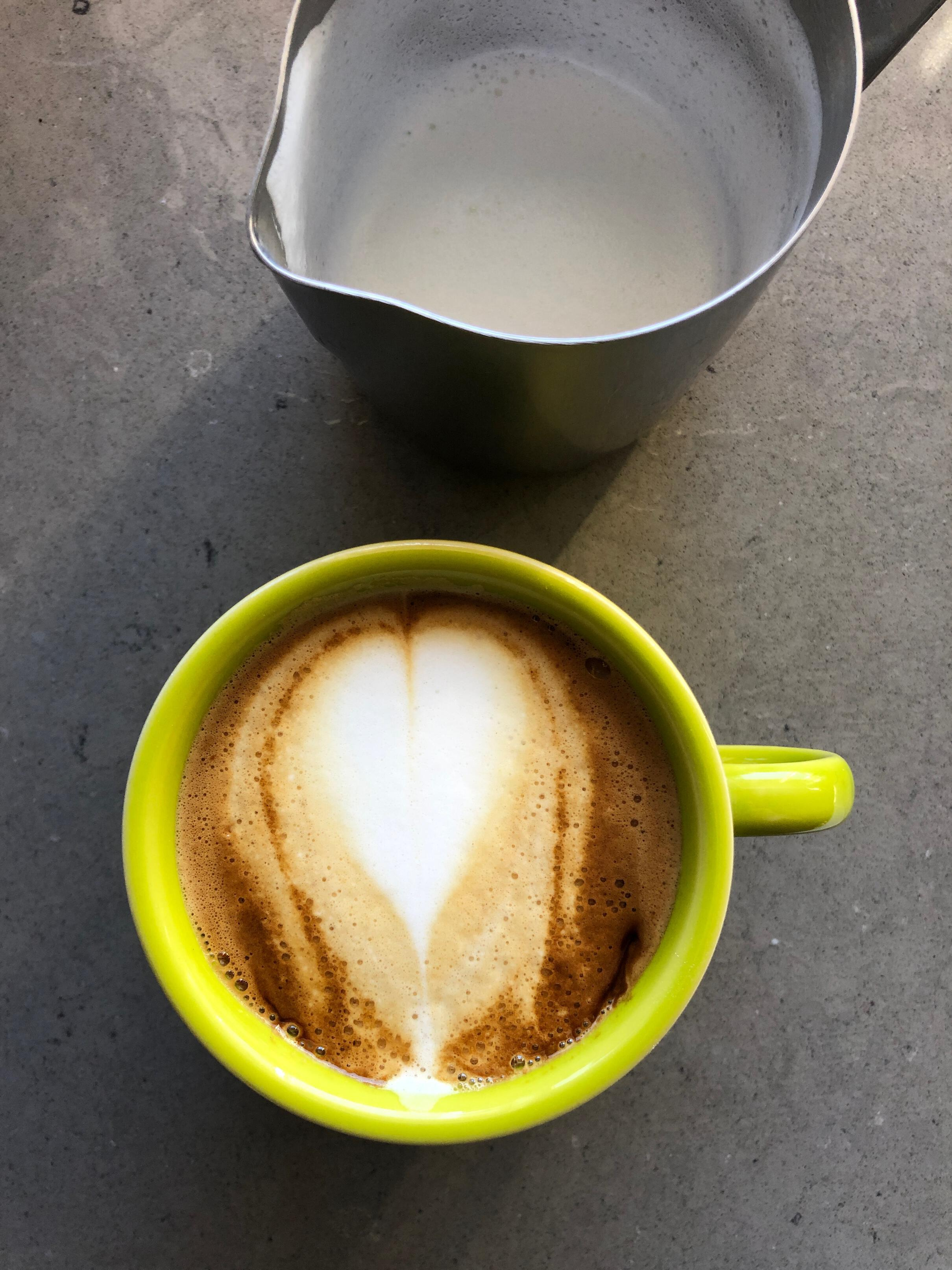Photo of a cappuccino with a heart-shaped pour of milk.