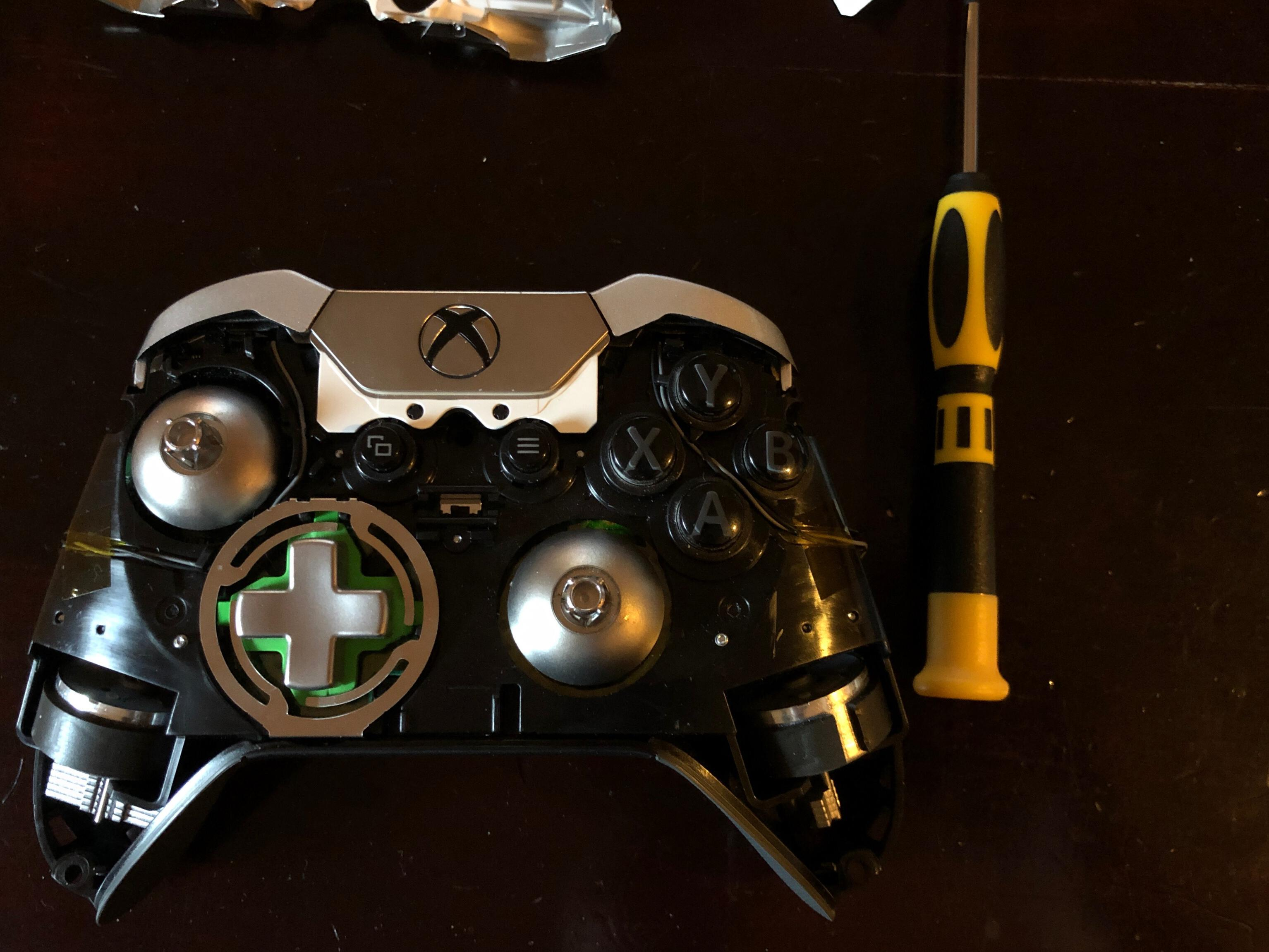 Photo of a game controller with top shell removed to expose internal mechanisms.
