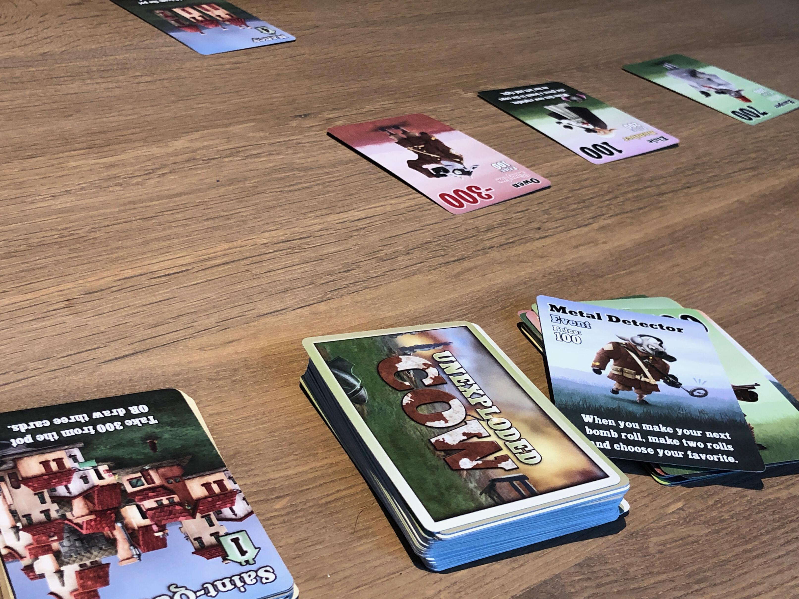 Photo of several cards for the game Unexploded Cow on a table.