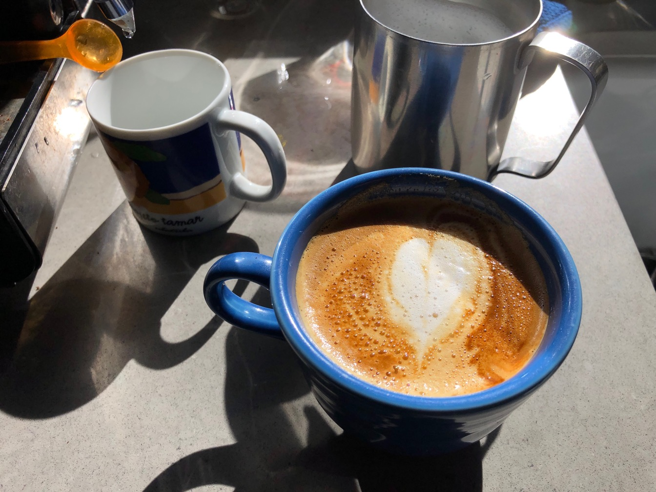 Photo of a cappuccino in a blue cup.