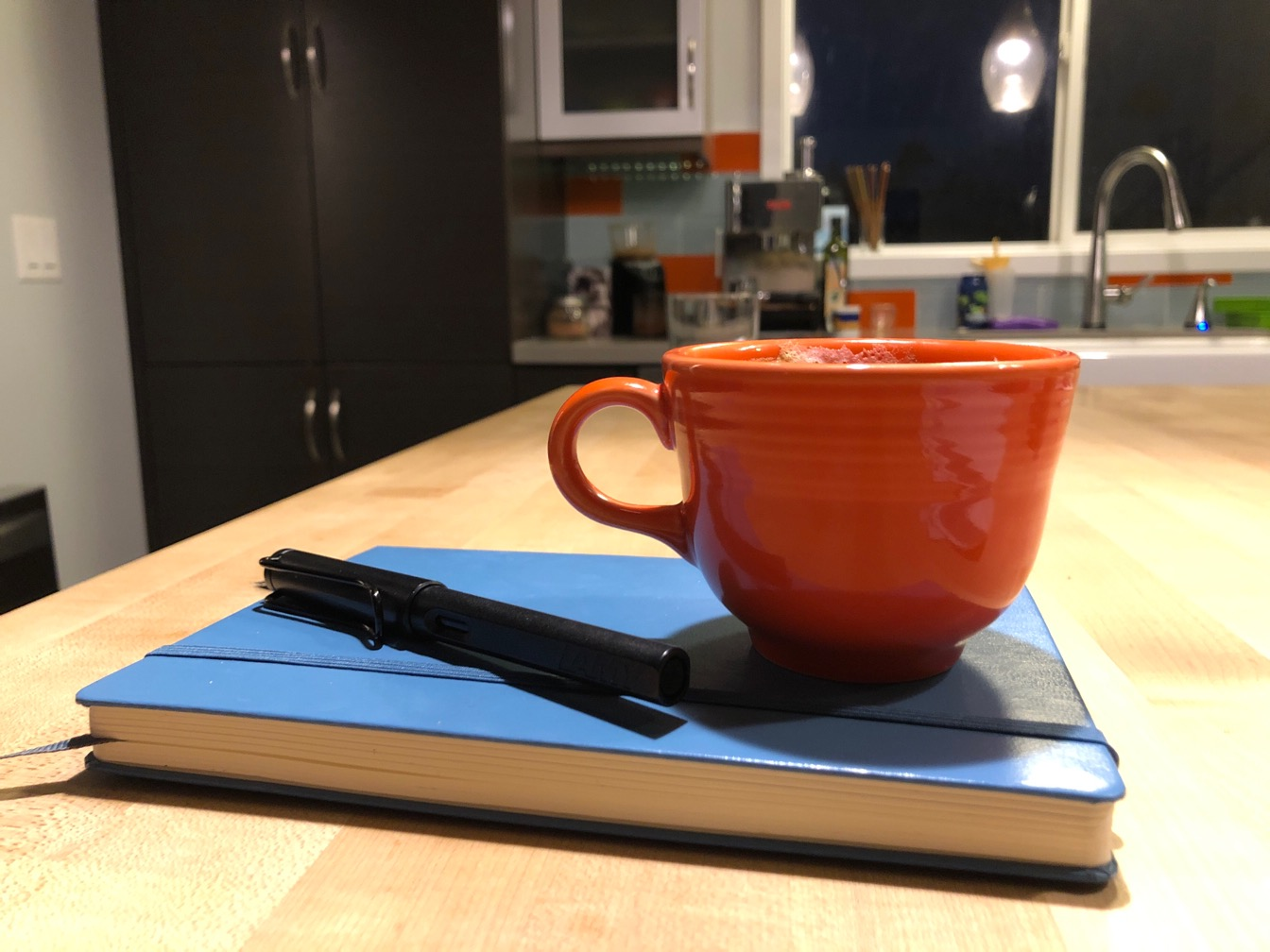 Photo of an orange coffee cup and a blue journal on a countertop.