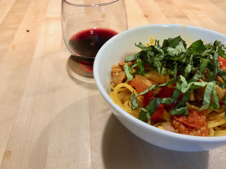 Photo of a bowl of spaghetti with tomatoes and calamari