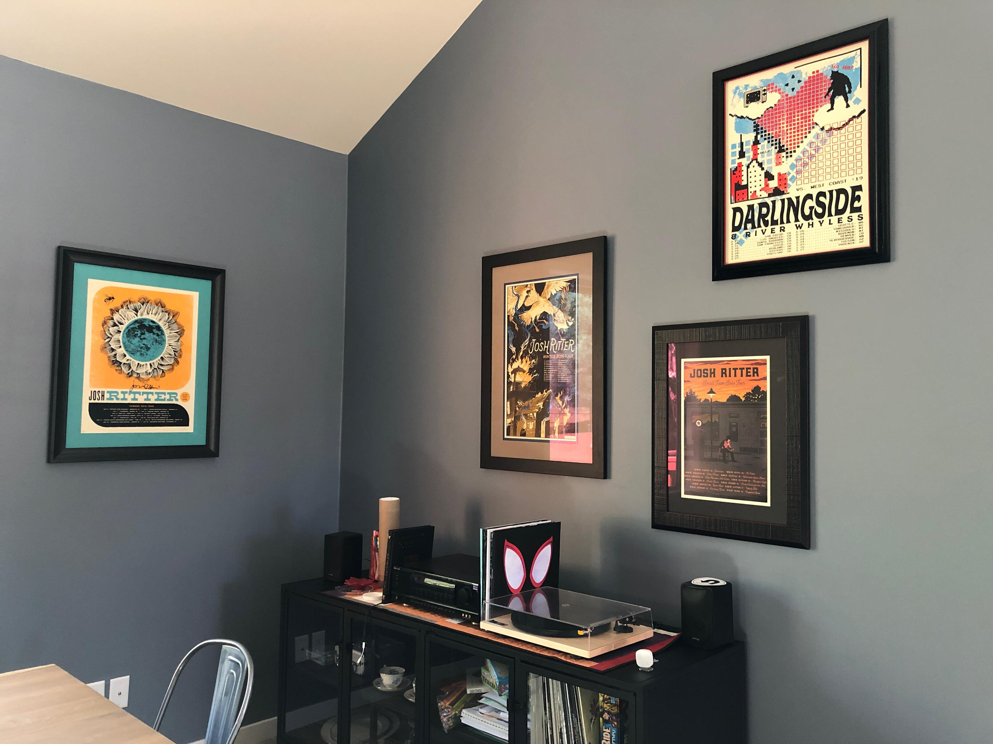 Framed Josh Ritter and Darlingside concert photos on a wall