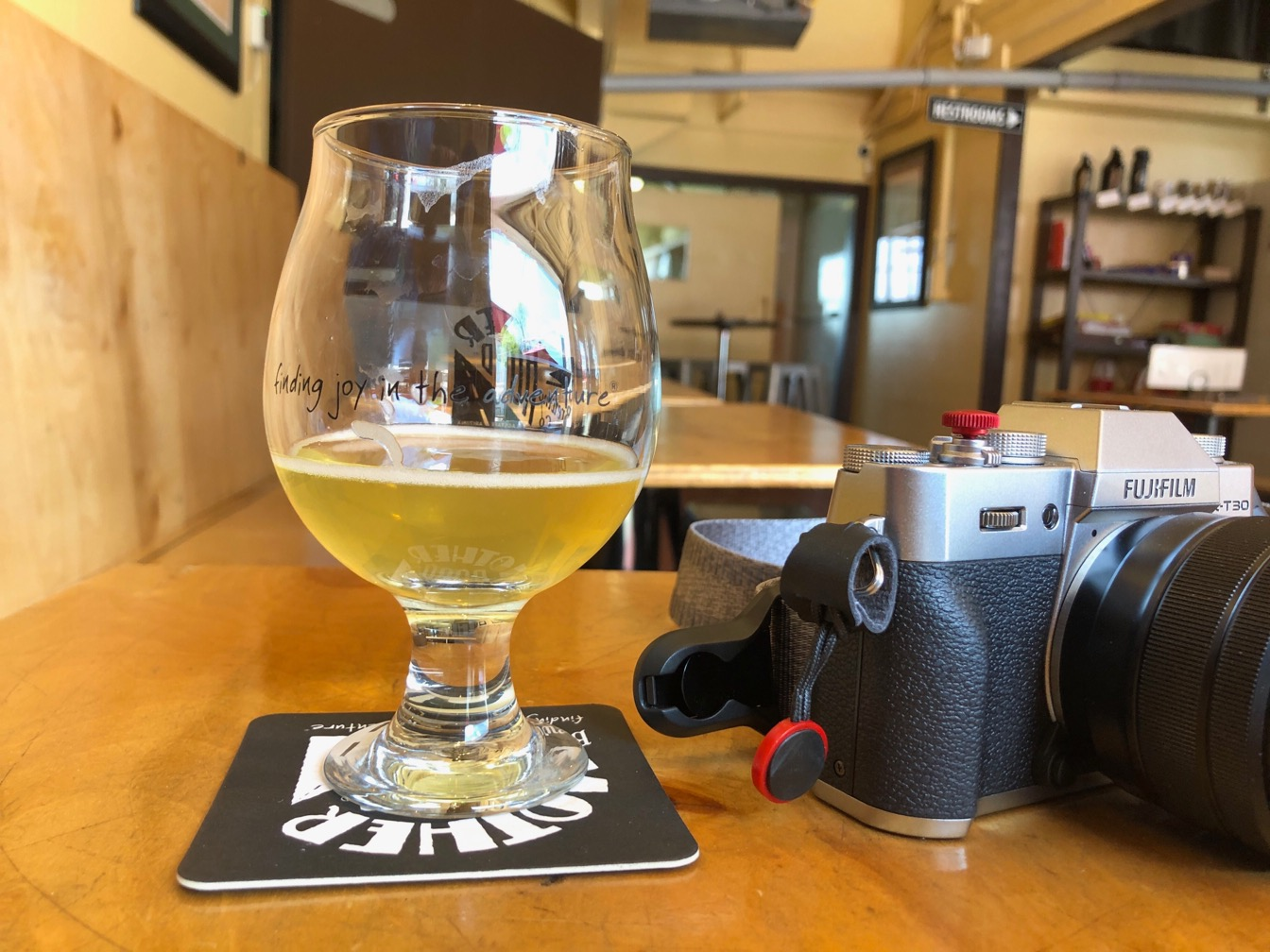 Photo of a tulip shaped beer glass with a Fiji camera next to it