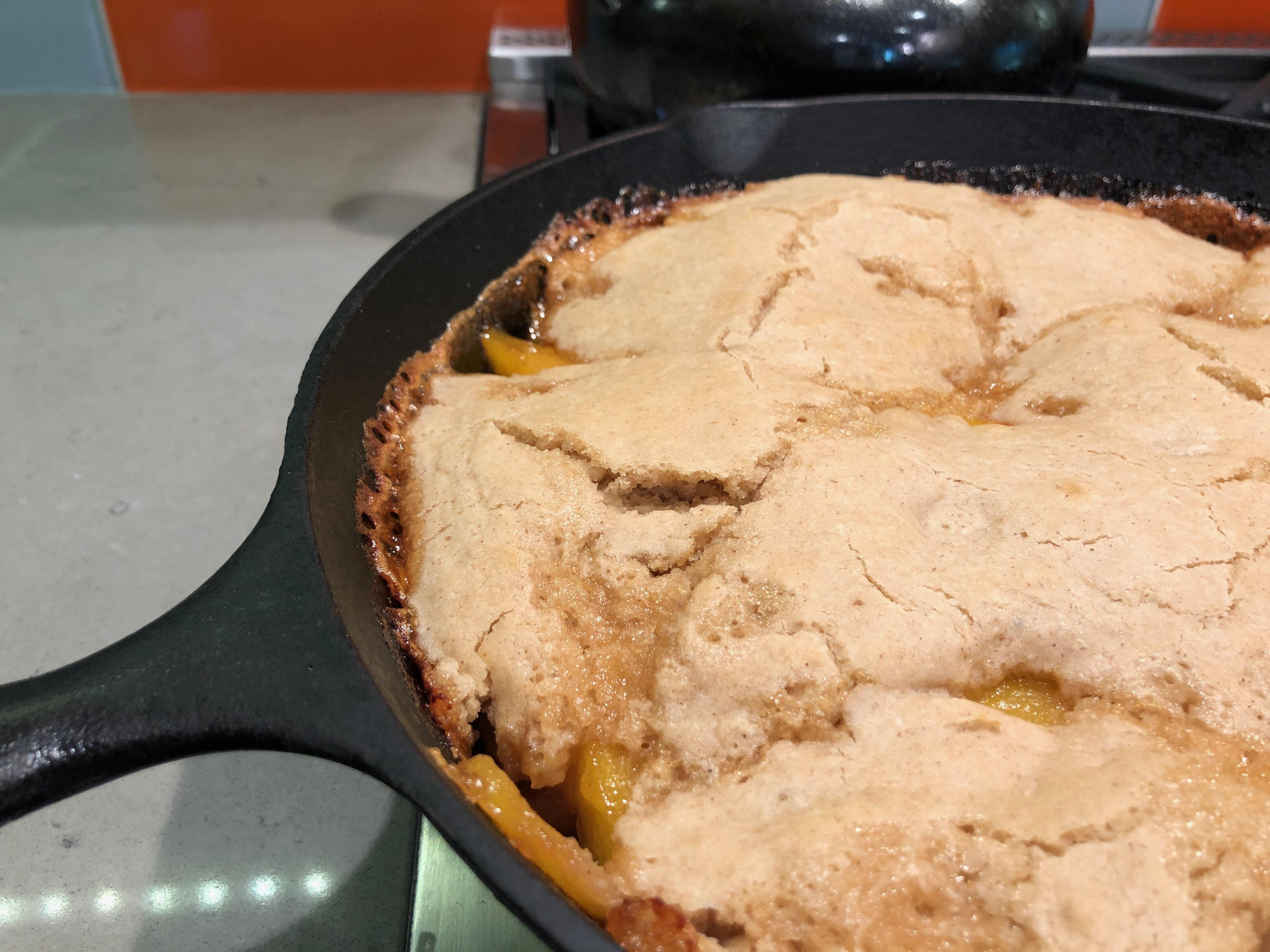Photo of bubbling peach cobbler in a cast iron pan.