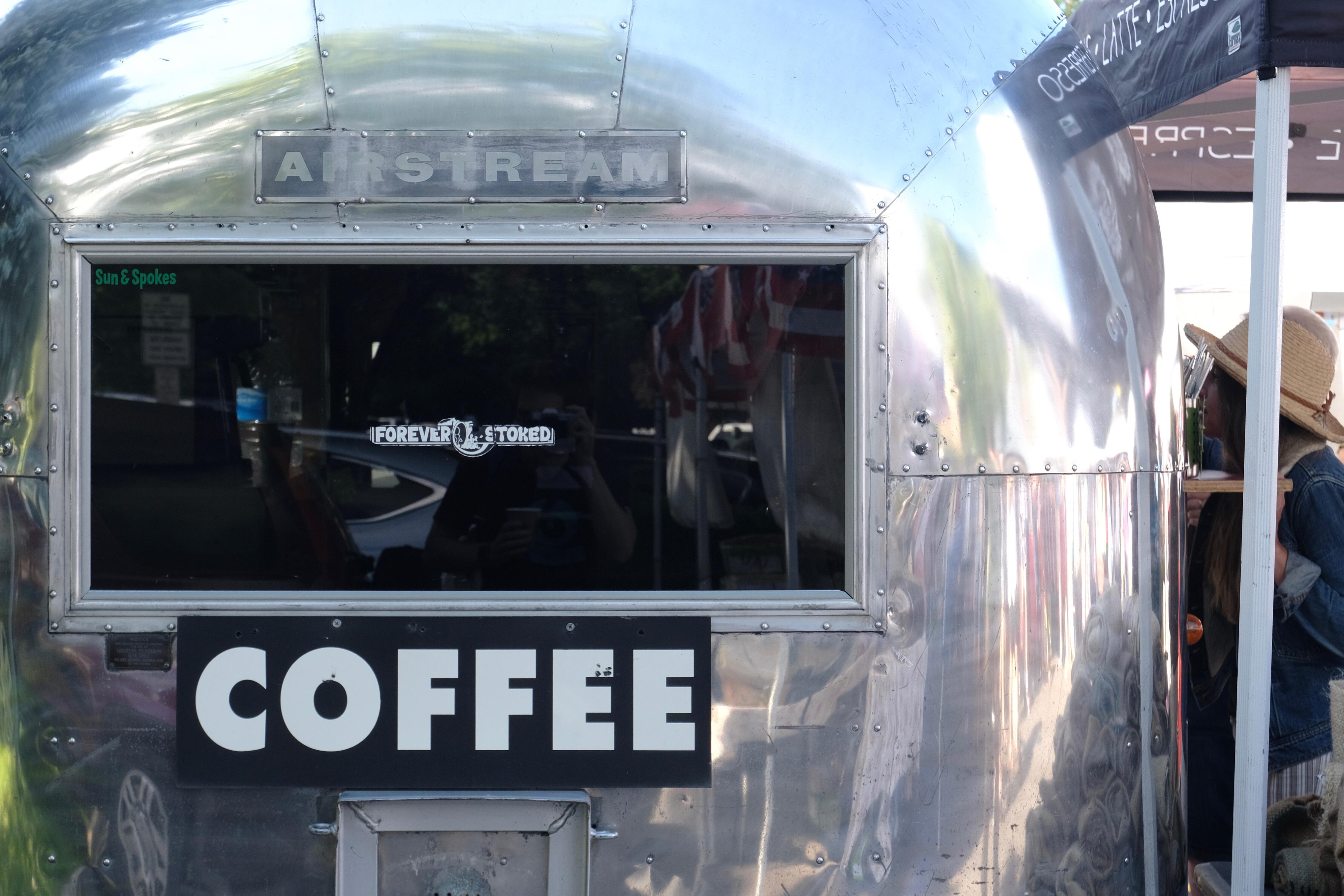 Shiny Airstream trailer with a COFFEE sign and reflective window