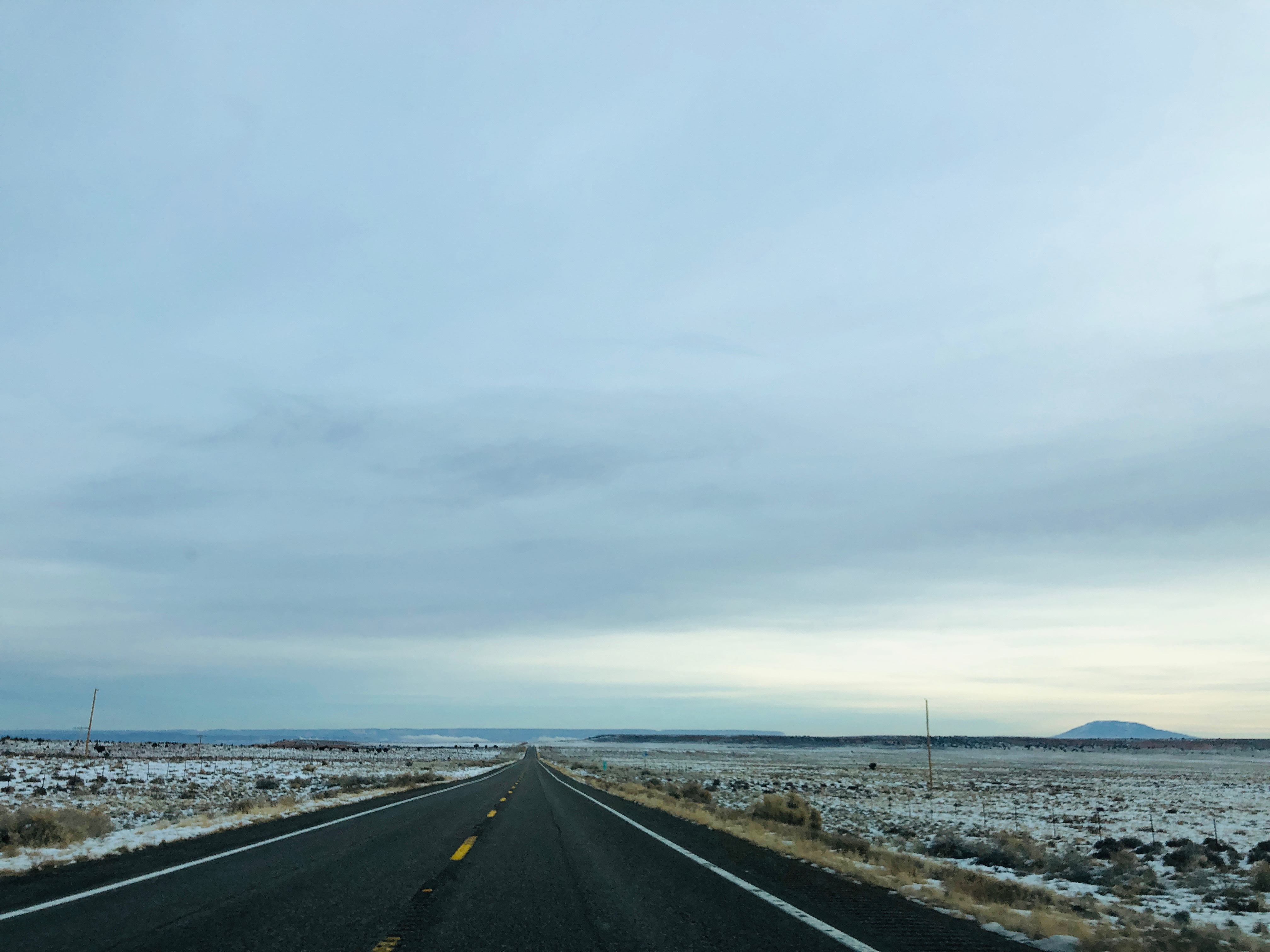 Photo of two-lane highway with light snow on each side and a cloudy sky