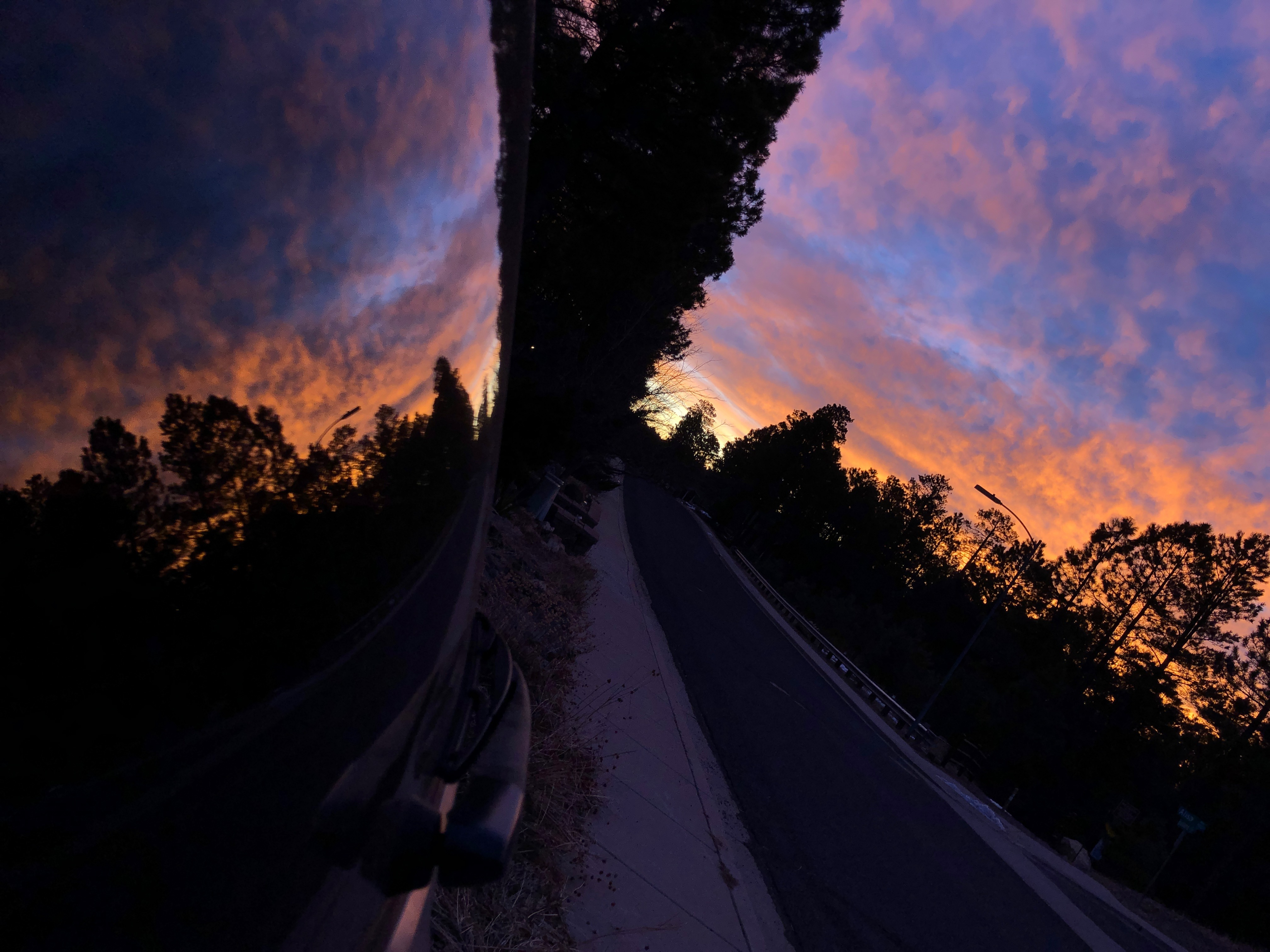 Photo of an orange and blue sunrise reflected in a car windshield