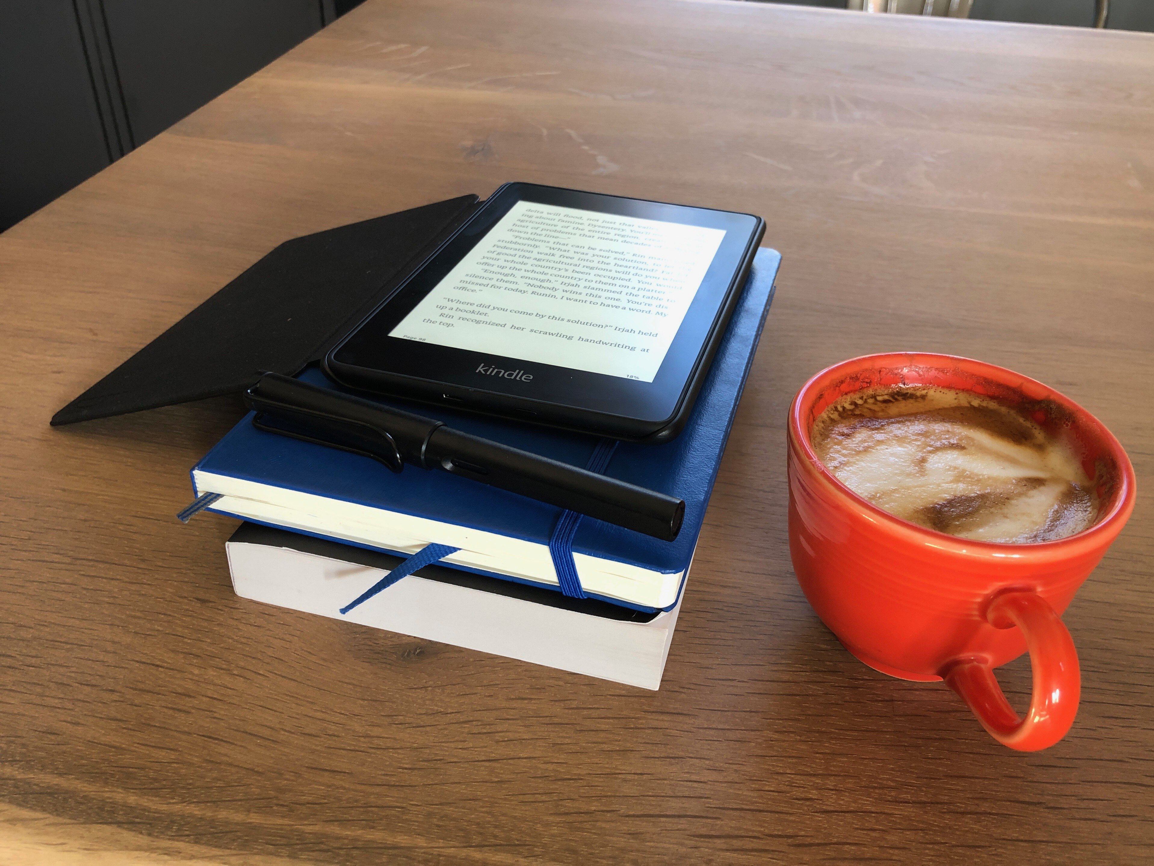 Cappuccino in an orange cup, beside a stack of a Kindle, notebook, and paperback