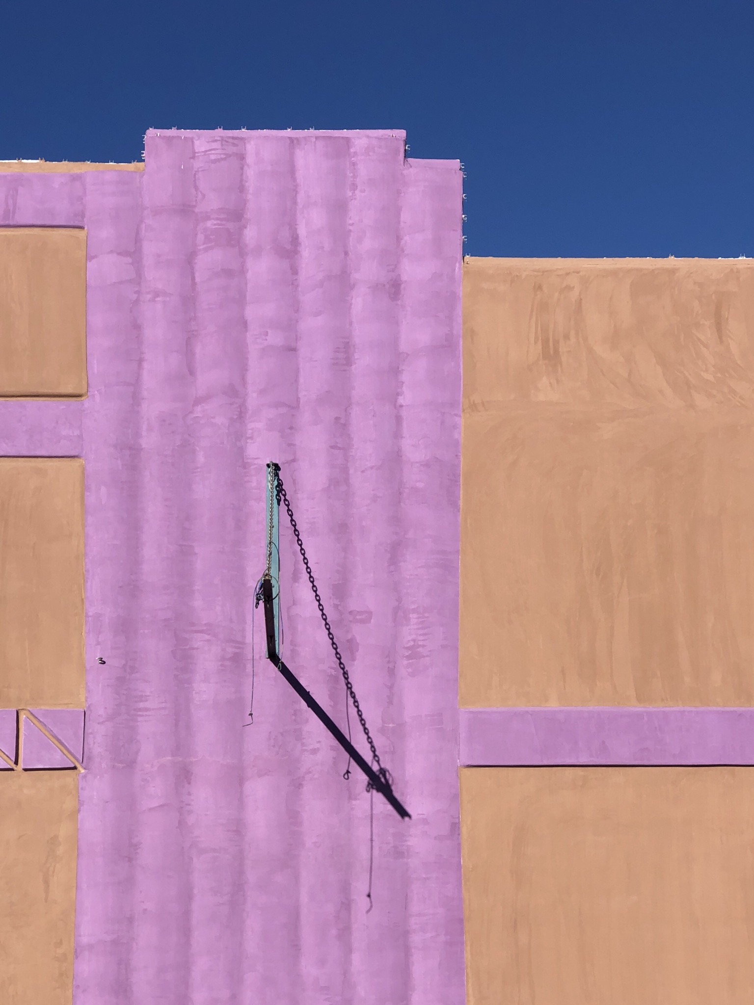 A terra cotta colored wall with pink stripes and a sharp black shadow across it