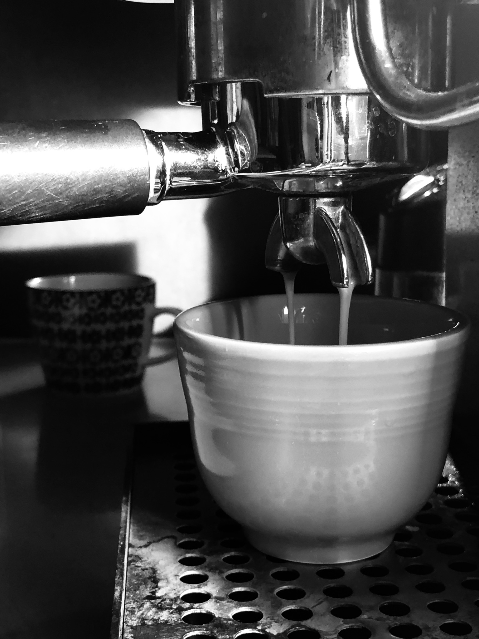 Black and white photo of an espresso shot pouring into a cup