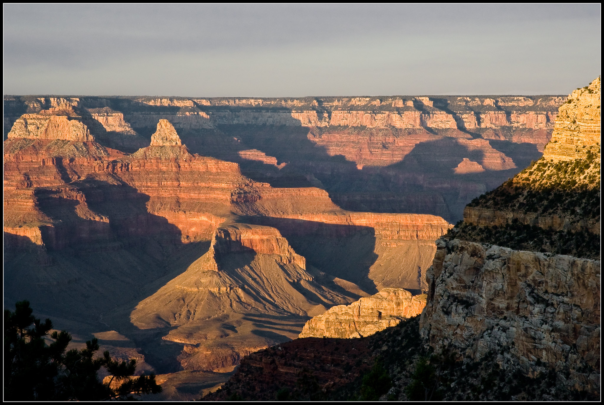 Photo of shadows cutting across the depths of the Grand Canyon, lit with pink and orange sunset light.