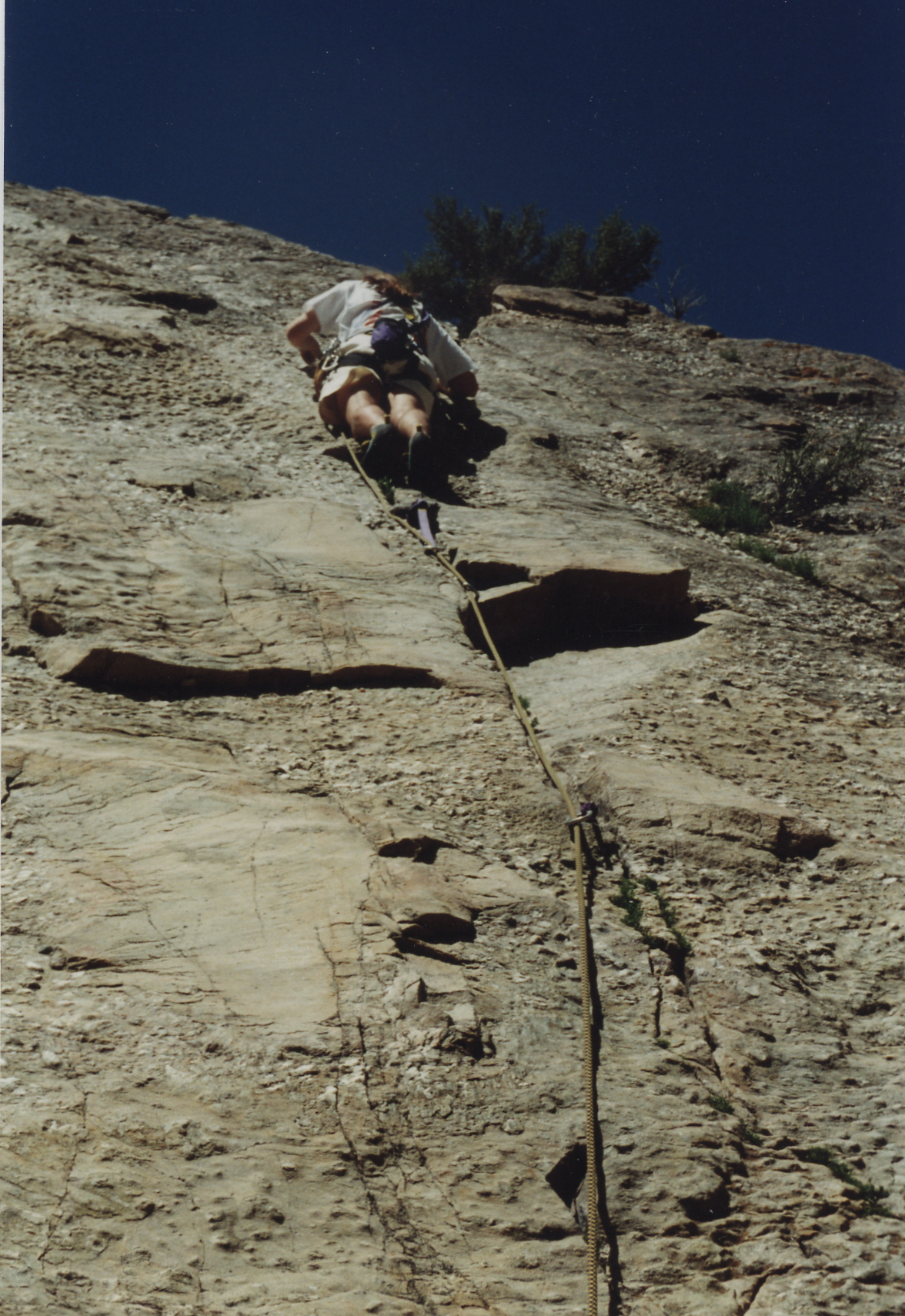 Photo of a climber leading up a wall, placing gear, rope below him.