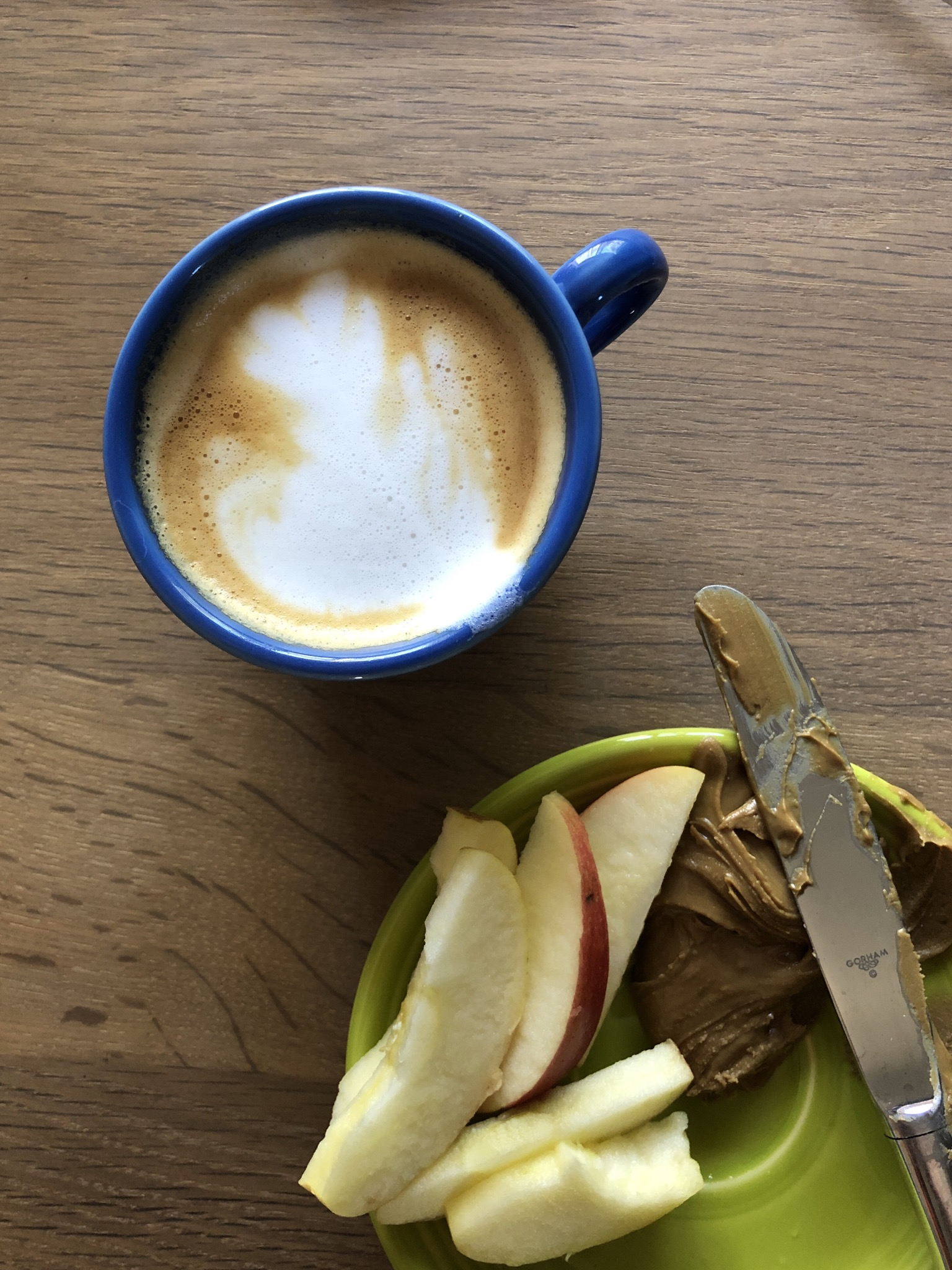 Photo of a coffee in a blue cup, apple slices and brown sunflower butter