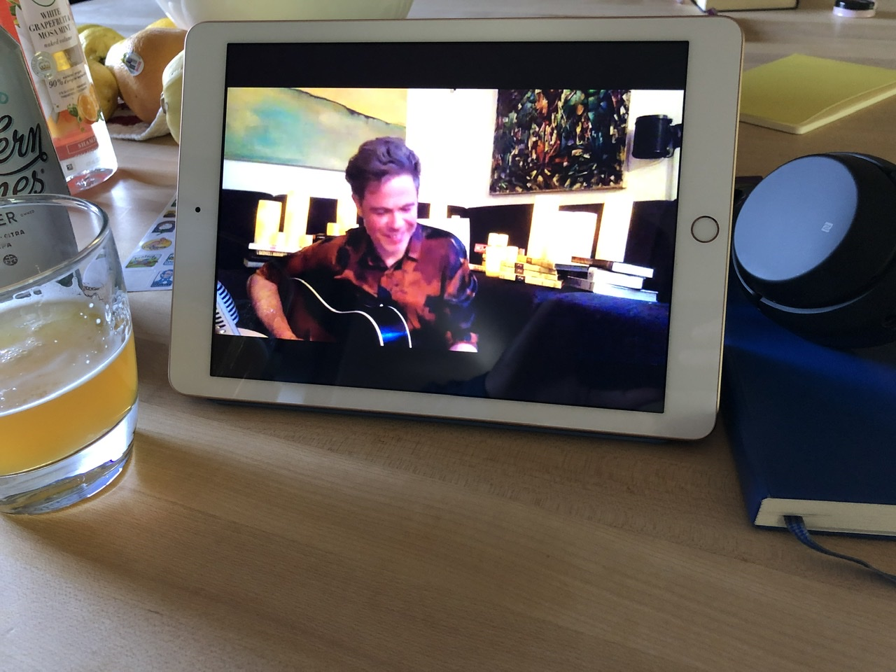 Photo of an iPad on a wooden counter, showing Josh Ritter playing a guitar