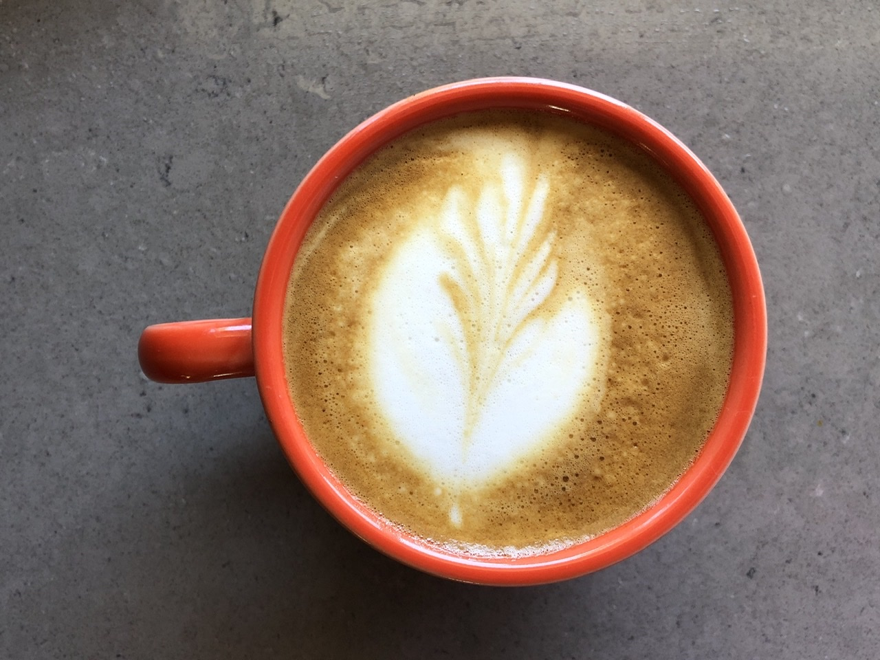 Top-down photo of a cappuccino in an orange mug