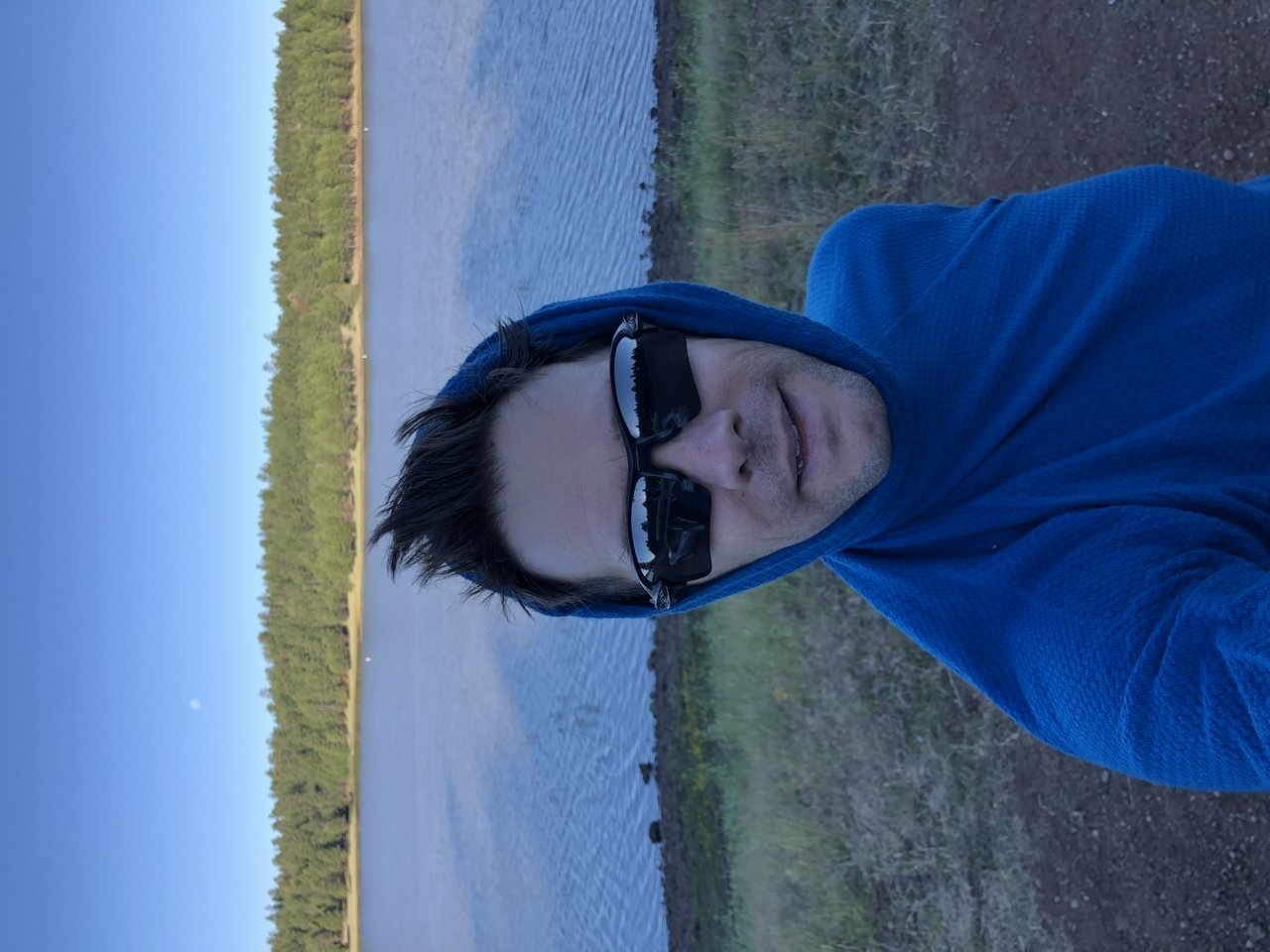 Self portrait in a pullover blue hoodie in front of shady lake