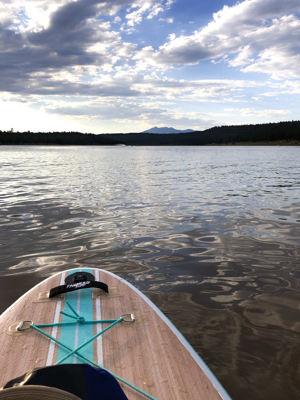 Bow of a paddleboard with low sun reflecting off the water and a tall peak in the far distance