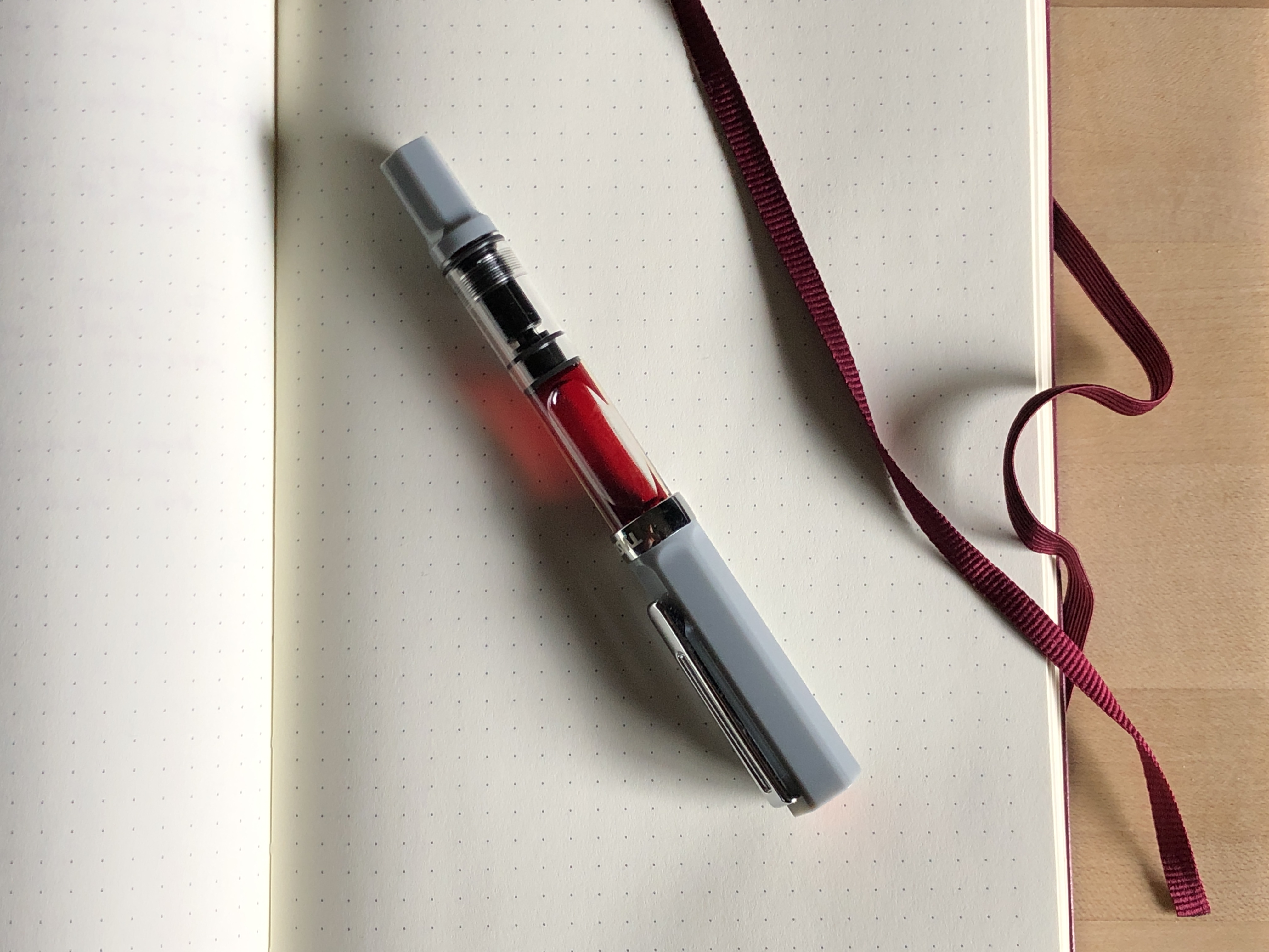 A pen with a clear barrel and filled with orange ink sitting on a notebook page.