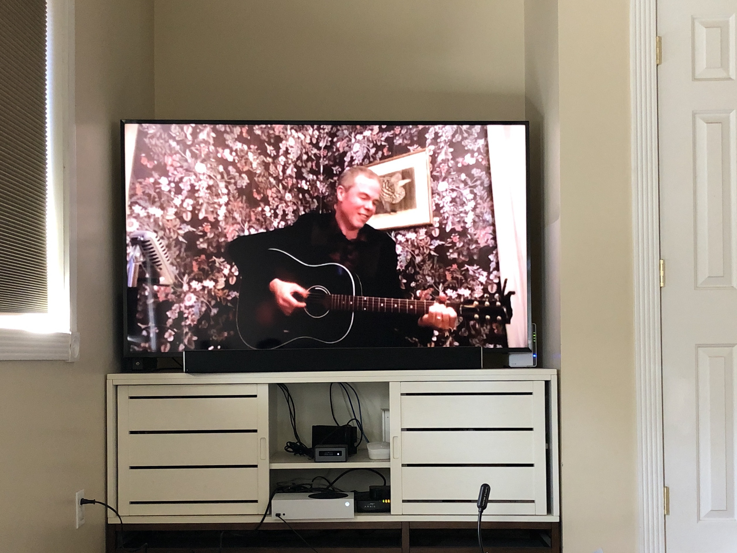 Photo of a TV screen showing Josh Ritter playing a guitar and smiling