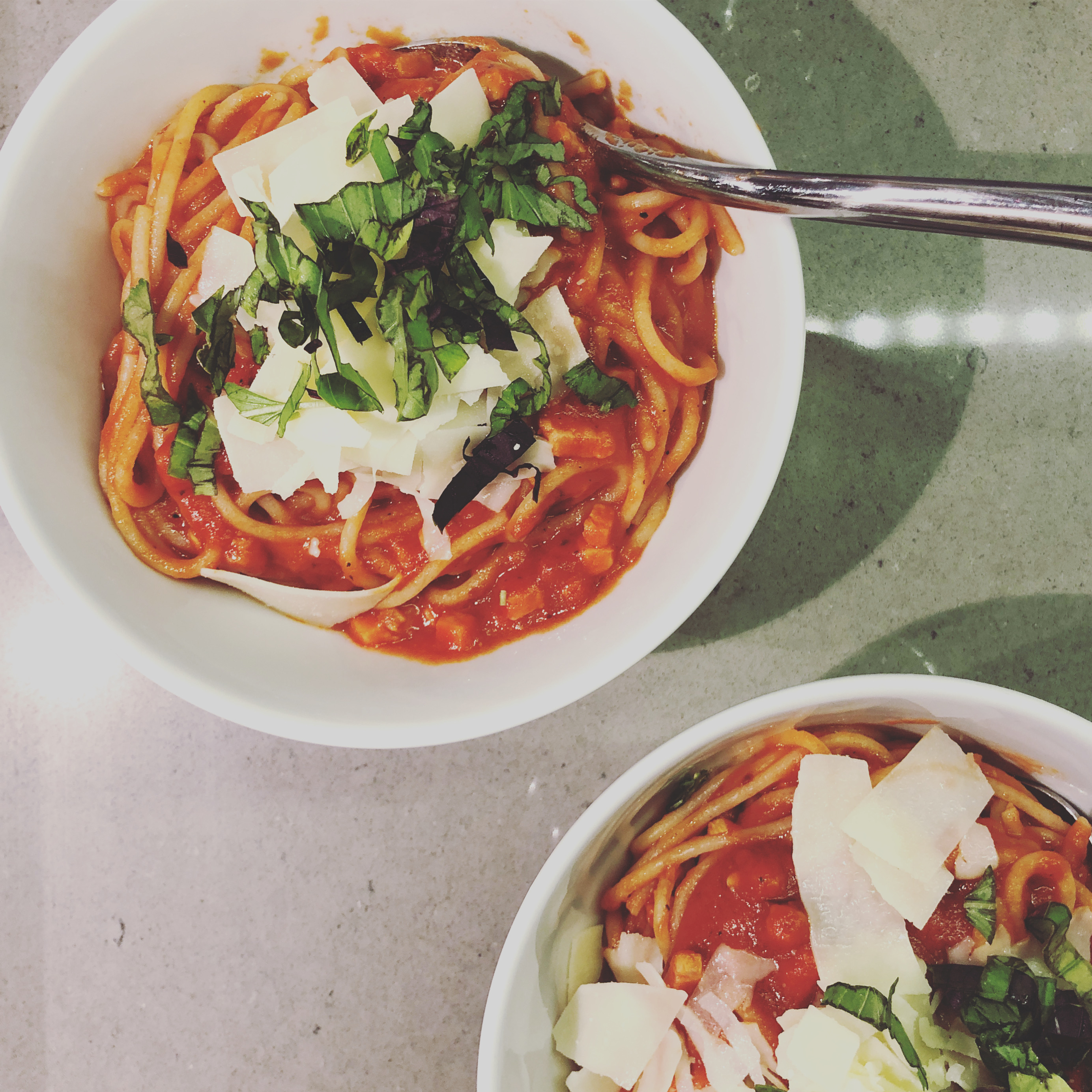 Two white bowls of spaghetti with tomato sauce, strips of cheese and shreds of bright green basil