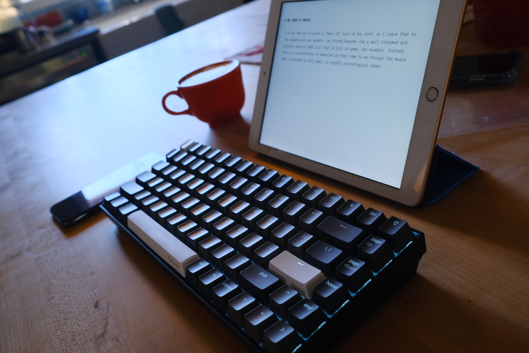 An iPad propped behind a dark gray and white keyboard, beside an orange coffee cup