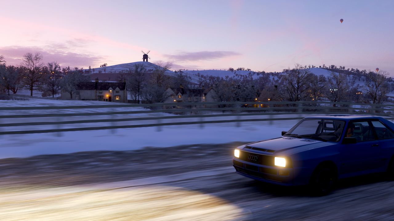 In-game photo of a blue car speeding along a dark snowy road, with warm house lights in the background