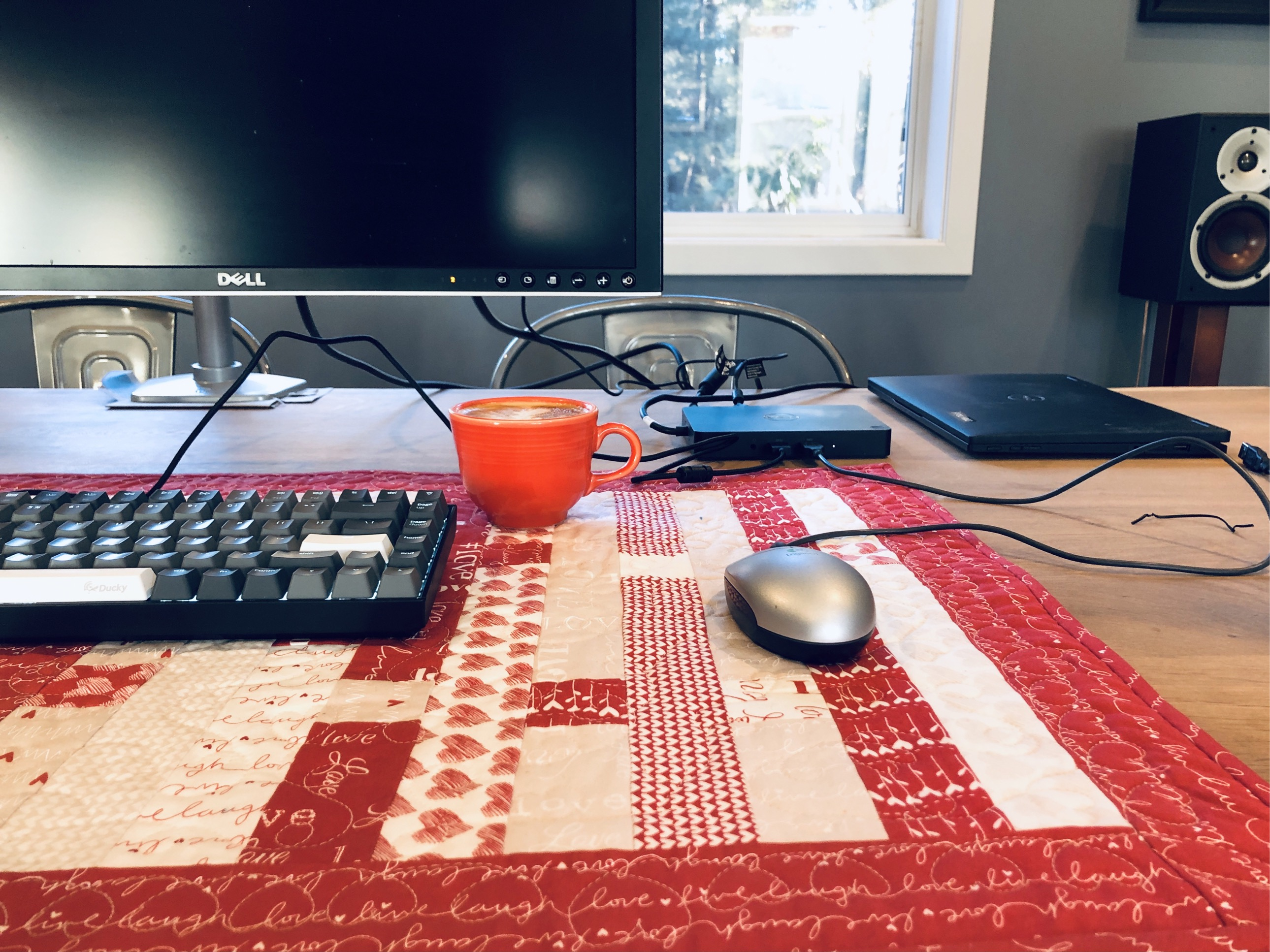A desk with monitor mounted on it, coffee cup and keyboard