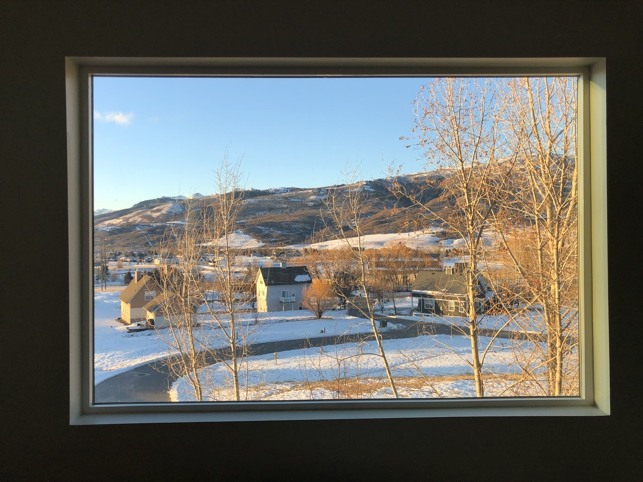A view out a large window, overlooking sunlit trees and snow, framed by a deep set window